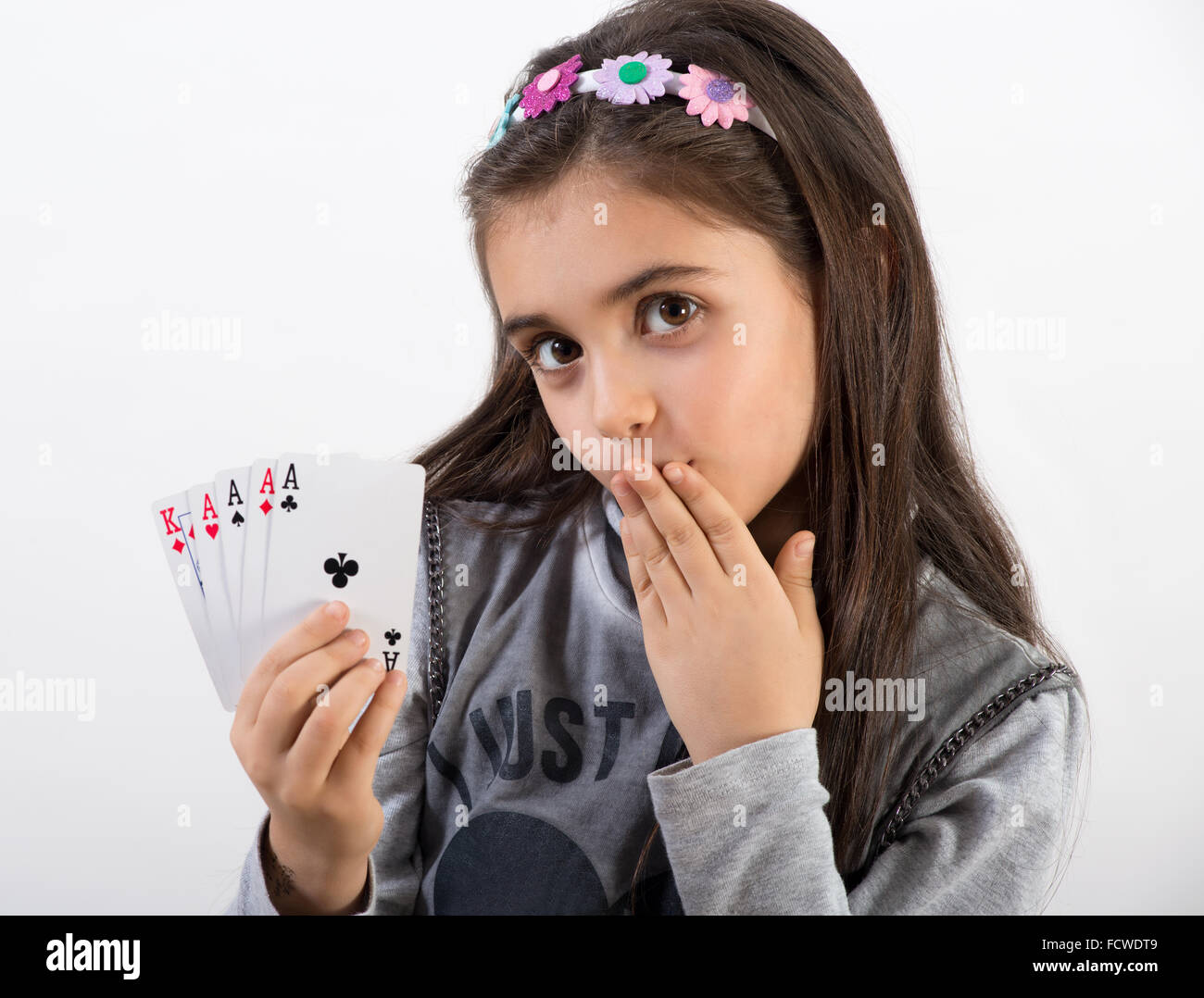 Secretive pretty young girl showing her winning poker hand - Stock Image
