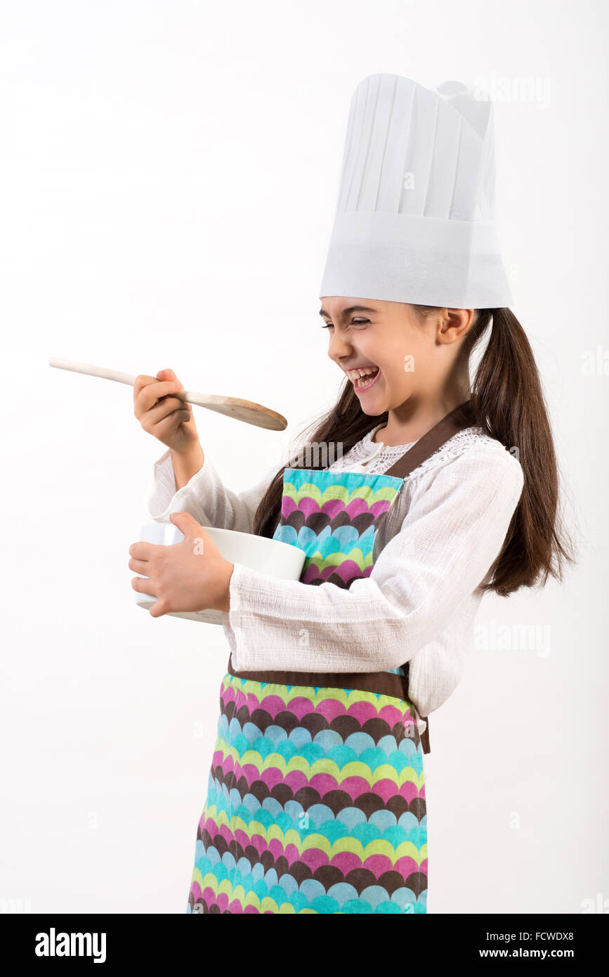 Cute little girl dressed as a chef in a white toque and colorful apron having fun laughing - Stock Image