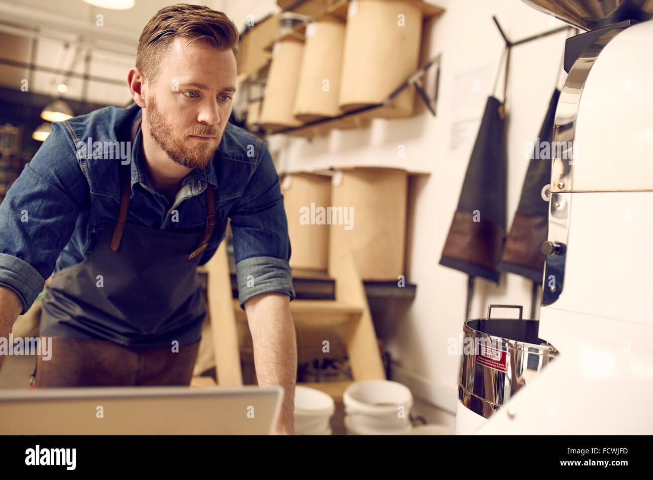 Entrepreneur working in his neat and modern coffee roastery - Stock Image