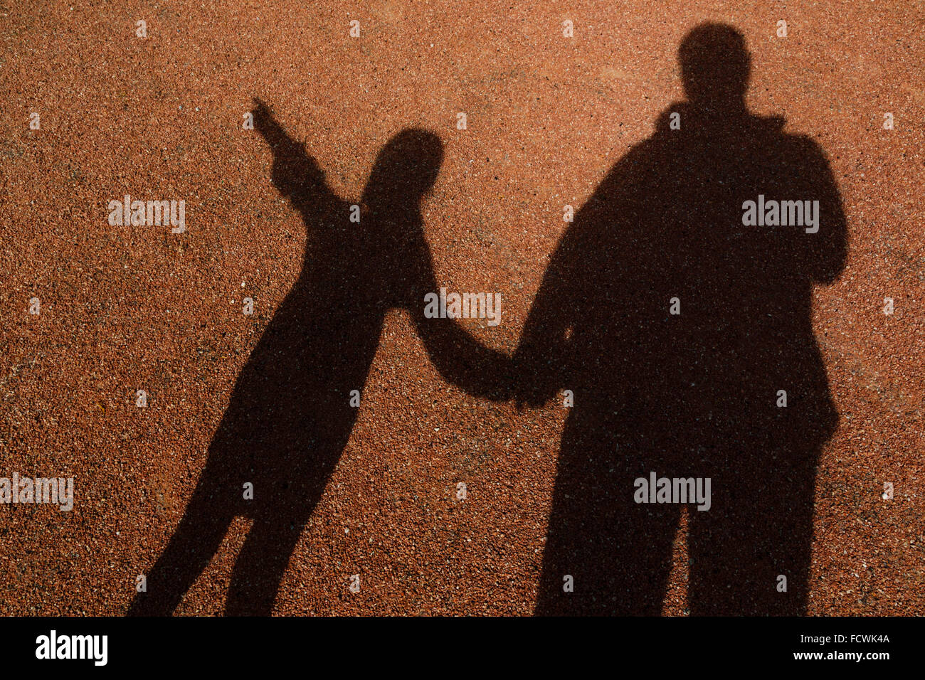 Shadows of adult and young female child holding hands. Little girl is pointing, - Stock Image