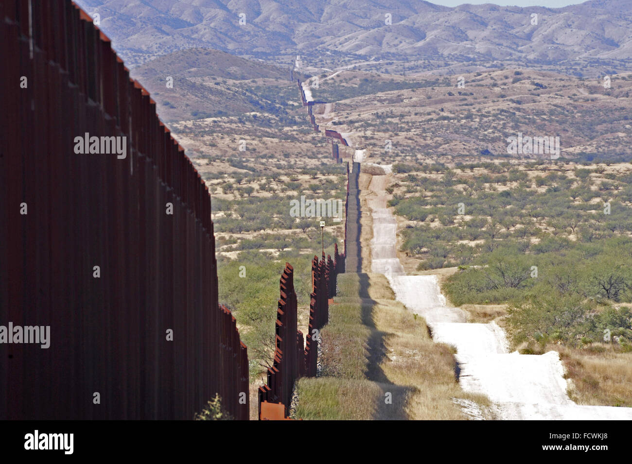 US border fence in Santa Cruz stretching into the distance leading to Nogales Sonora, Mexico and Santa Cruz County Stock Photo
