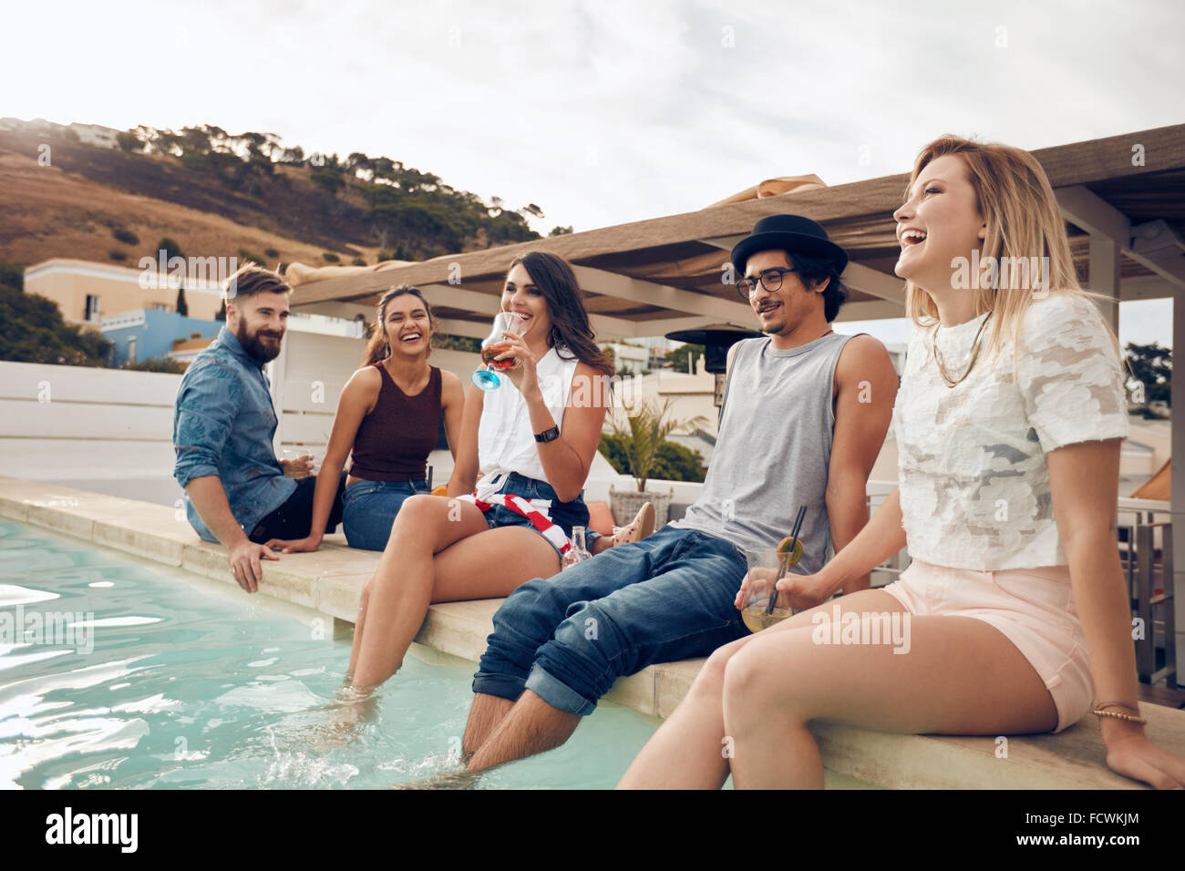 Young people drinking cocktails by the pool during party. Young friends laughing while sitting by a swimming pool. - Stock Image