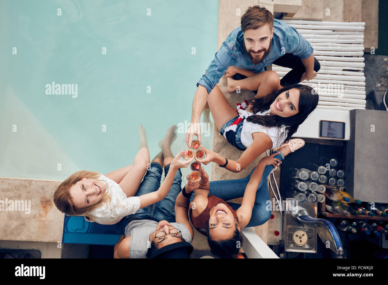 Overhead view of group of friends toasting at party by a swimming pool and looking up at camera smiling. Multiracial - Stock Image