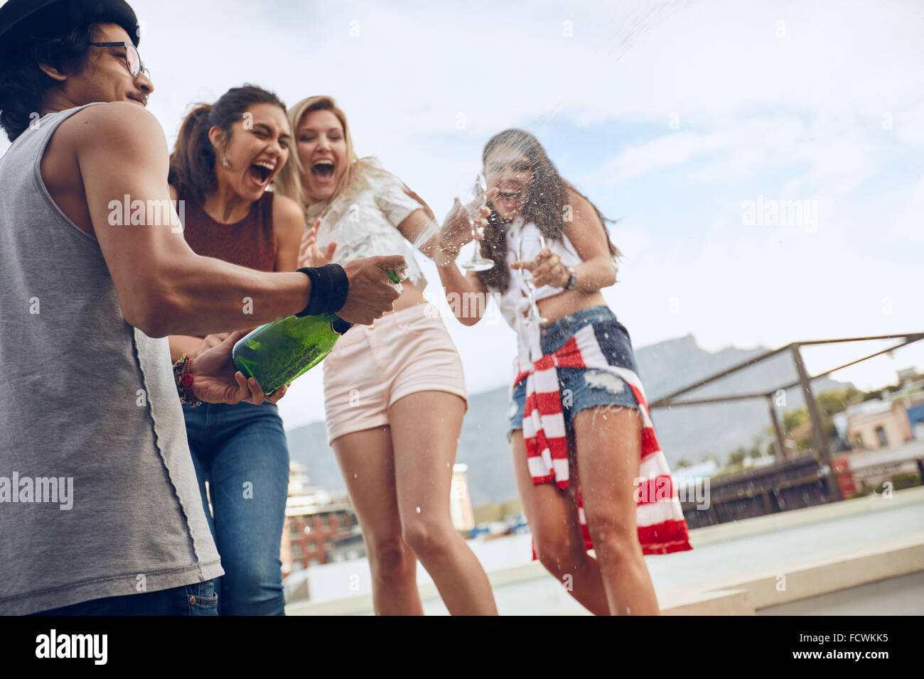 Young man opening a bottle of champagne with female friends standing in background laughing and having fun. Young - Stock Image