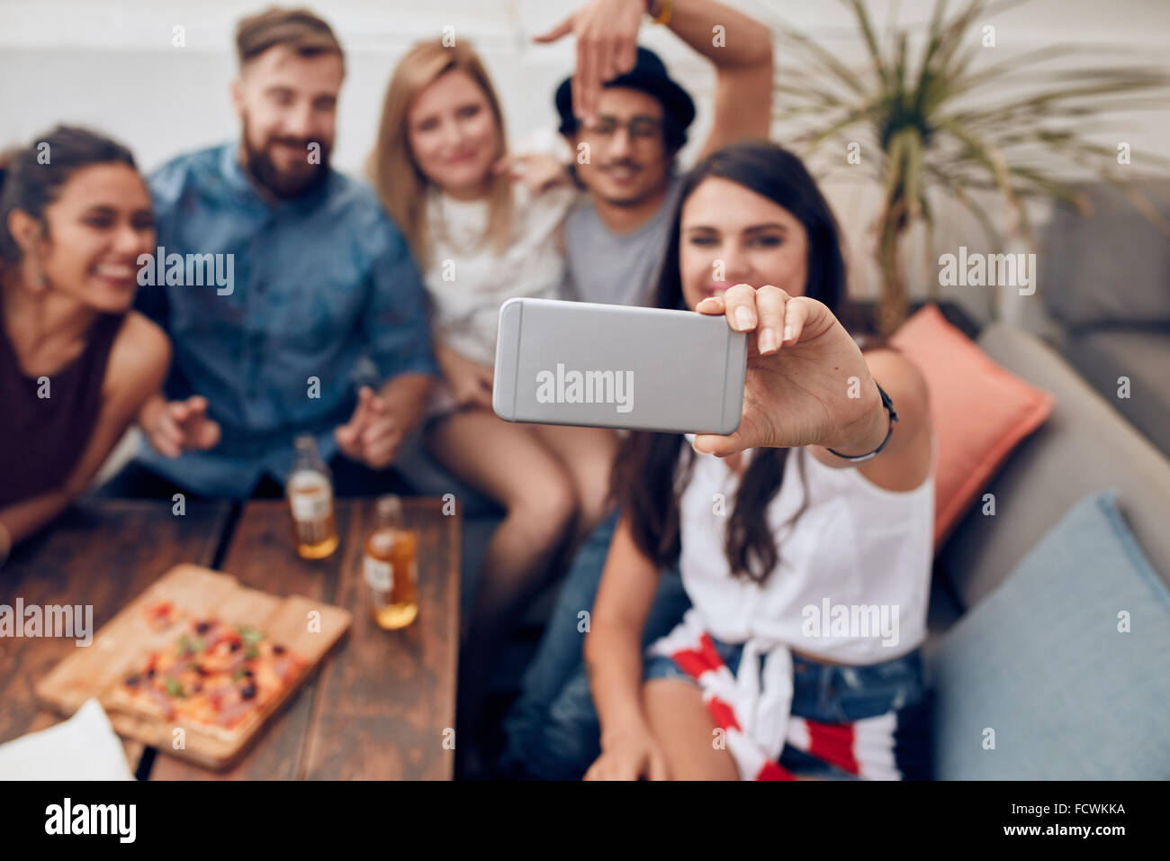 Young friends in a party taking self portrait with smart phone. Focus on mobile phone in woman's hand. Group of Stock Photo