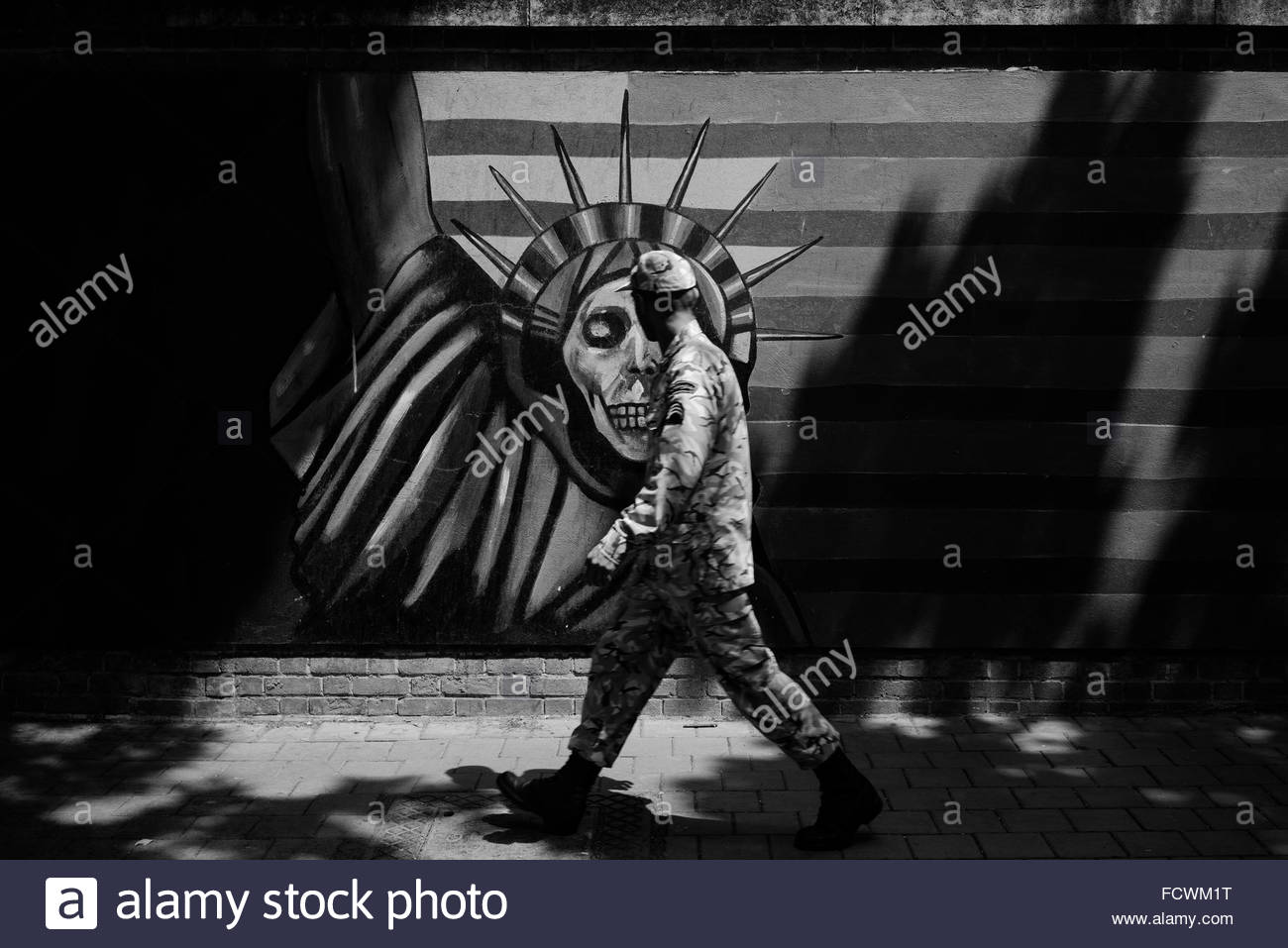 Iranian soldier looking at the Anti-American propaganda mural with an interpretation of the Statue of Liberty, at - Stock Image