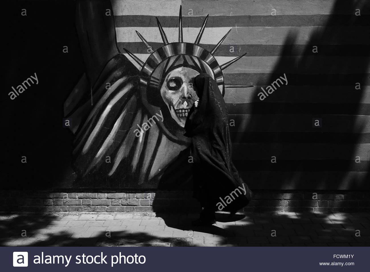 Iranian woman wearing a Chador walking past an Anti-American propaganda mural with an interpretation of the Statue - Stock Image