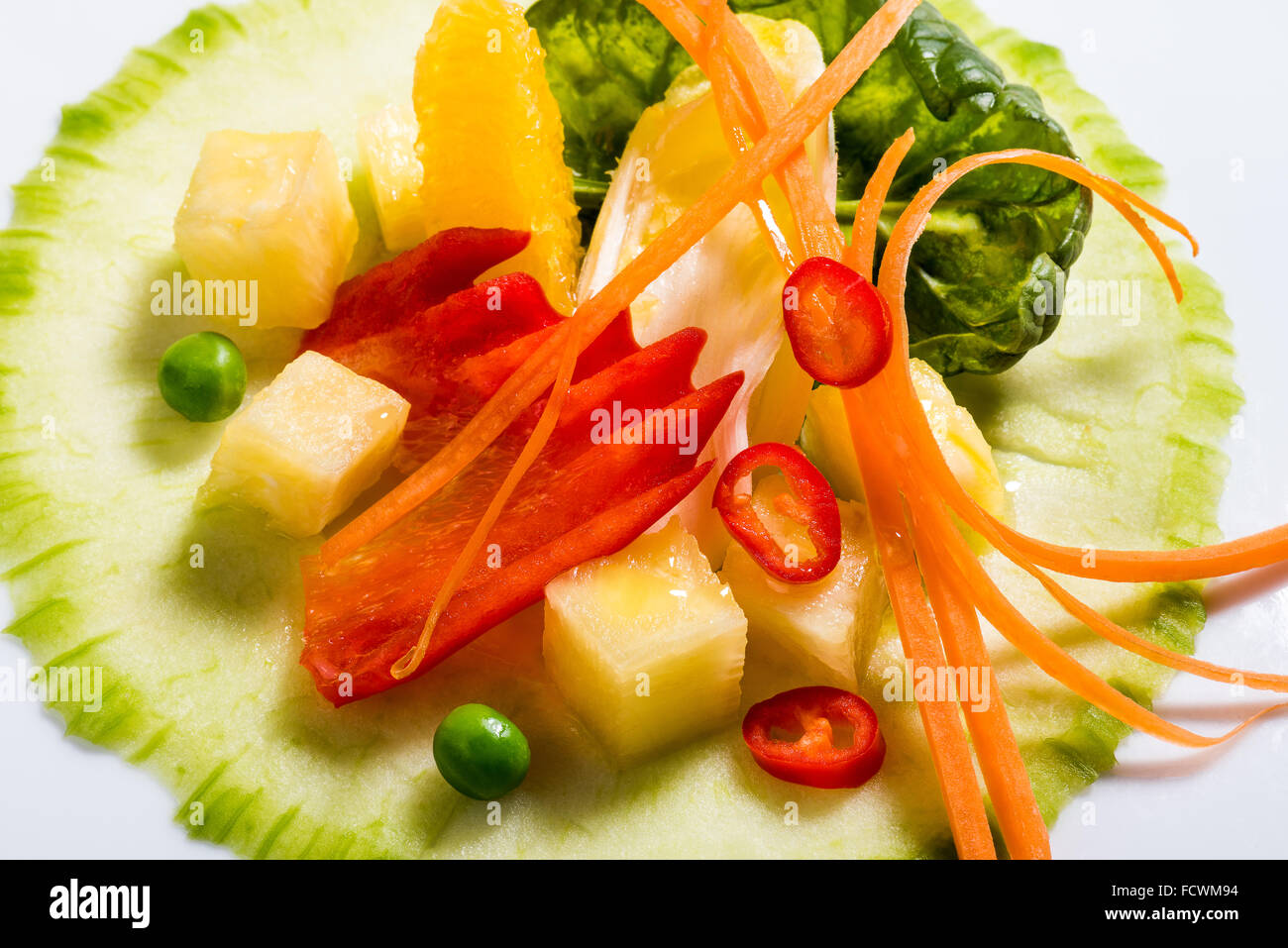 Salad Creation Fitness salad fresh on the plate. Cucumber, baby spinach, carrot, chicory, fresh pineapple, peppers, - Stock Image