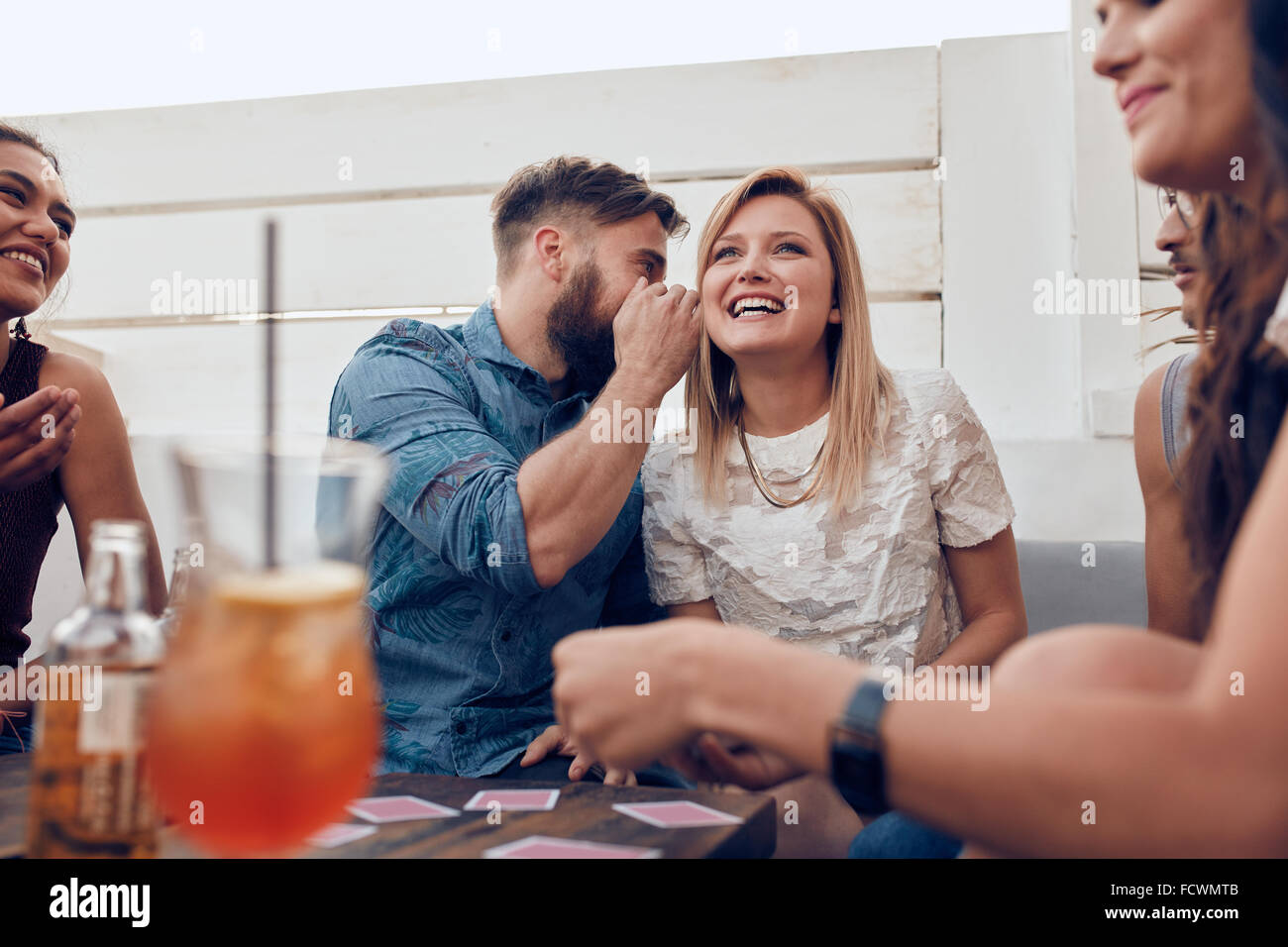 Young people sitting together in a party. Man whispering something in woman's ears. Sharing a secret. - Stock Image