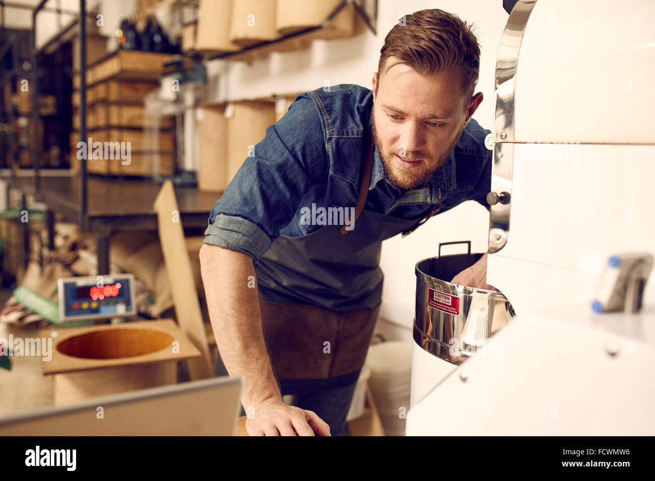 Man checking his laptop while operating a modern coffee roaster - Stock Image