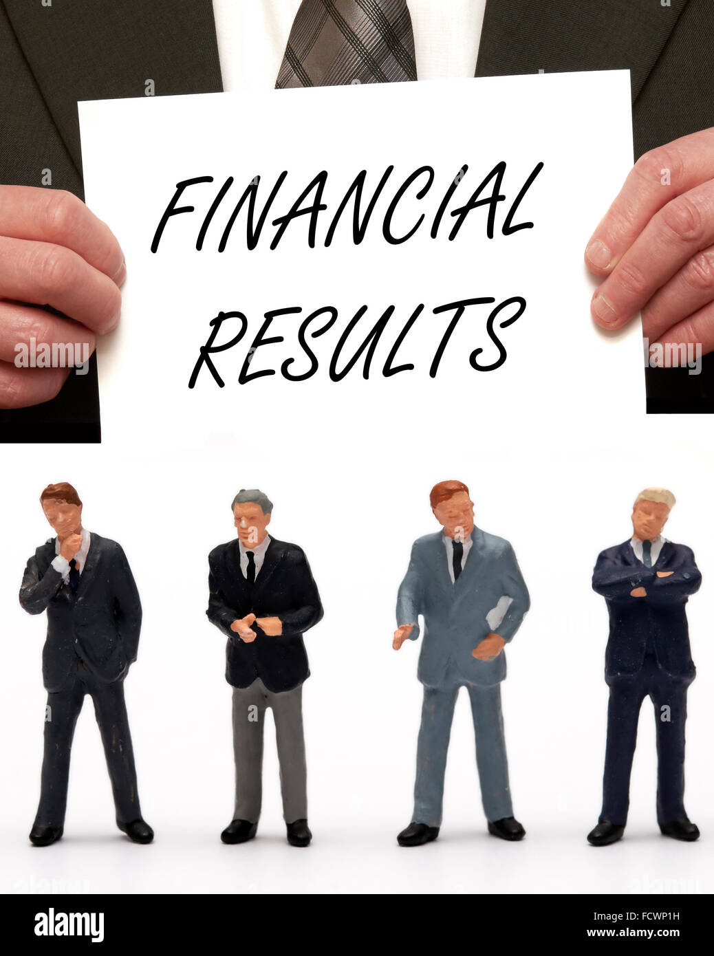 Miniature figurine Business men dressed in suits with the message Financial results on a card being held by a man - Stock Image