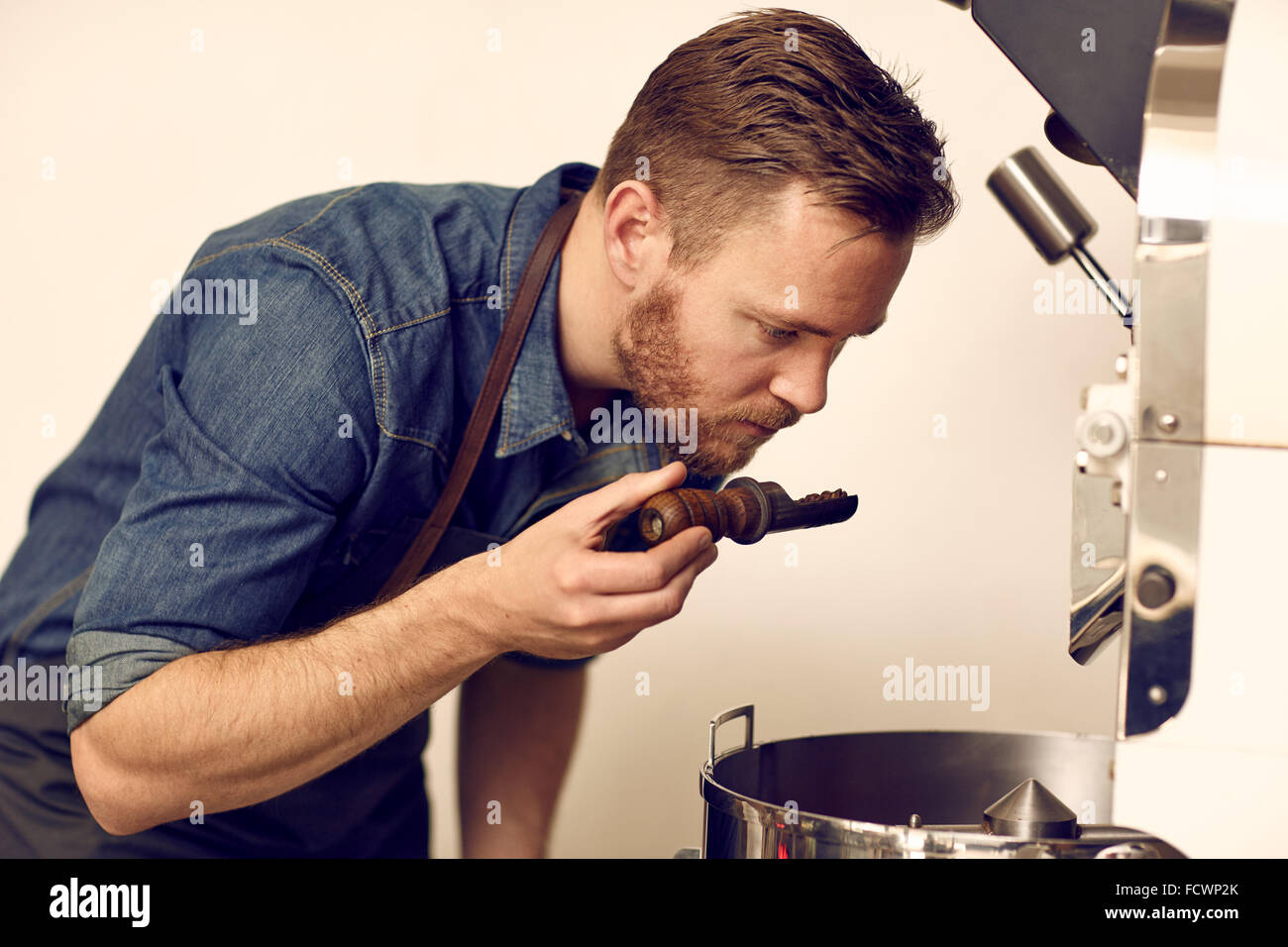 Coffee roaster smelling the aroma of some freshly roasted coffee - Stock Image