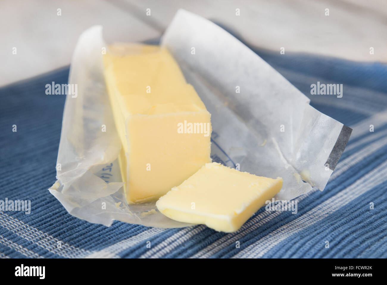 stick of fresh creamery butter in opened wrapper Stock Photo