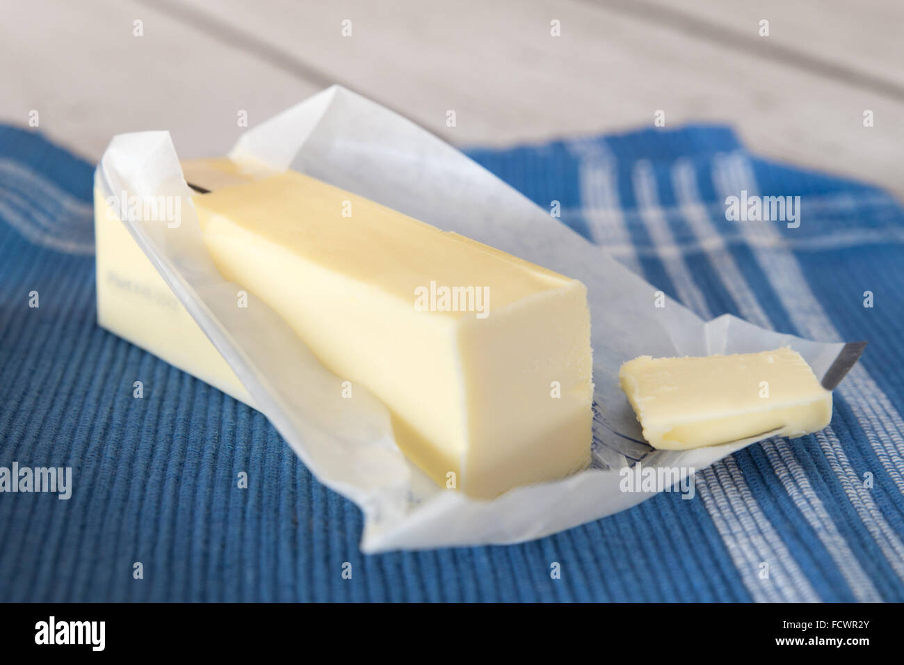 stick of fresh creamery butter in opened wrapper - Stock Image