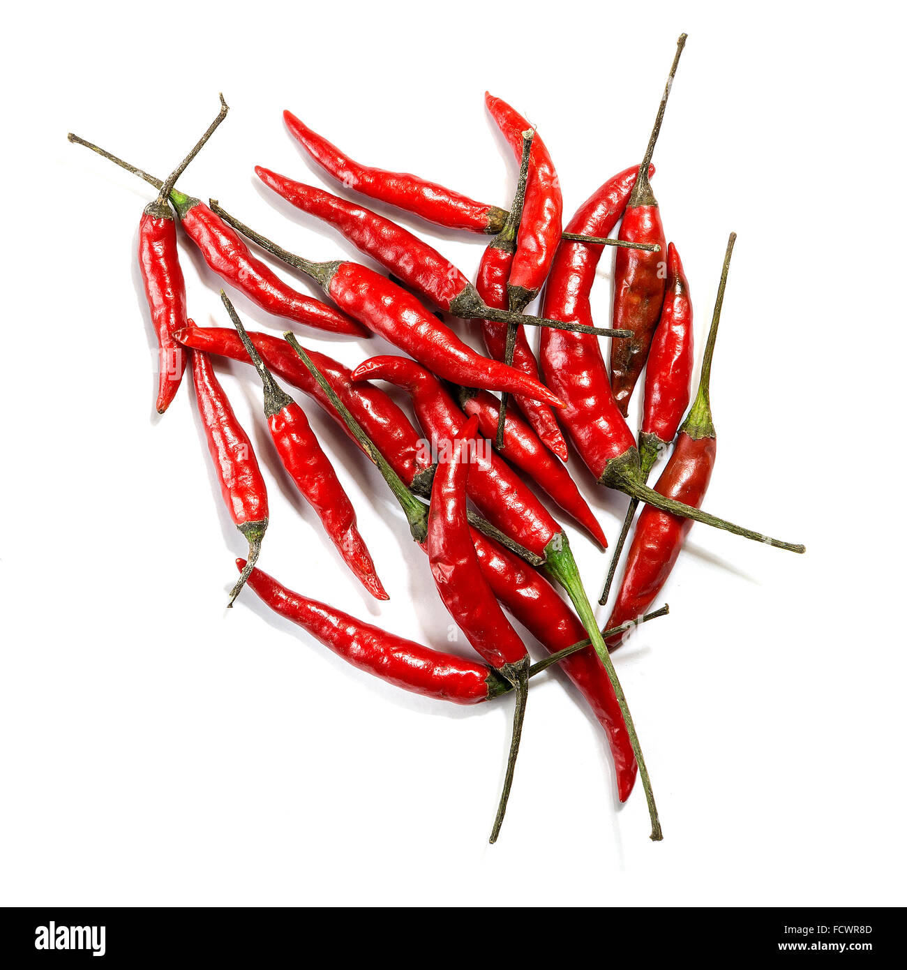 A group of red birds eye chillies on a white background - Stock Image