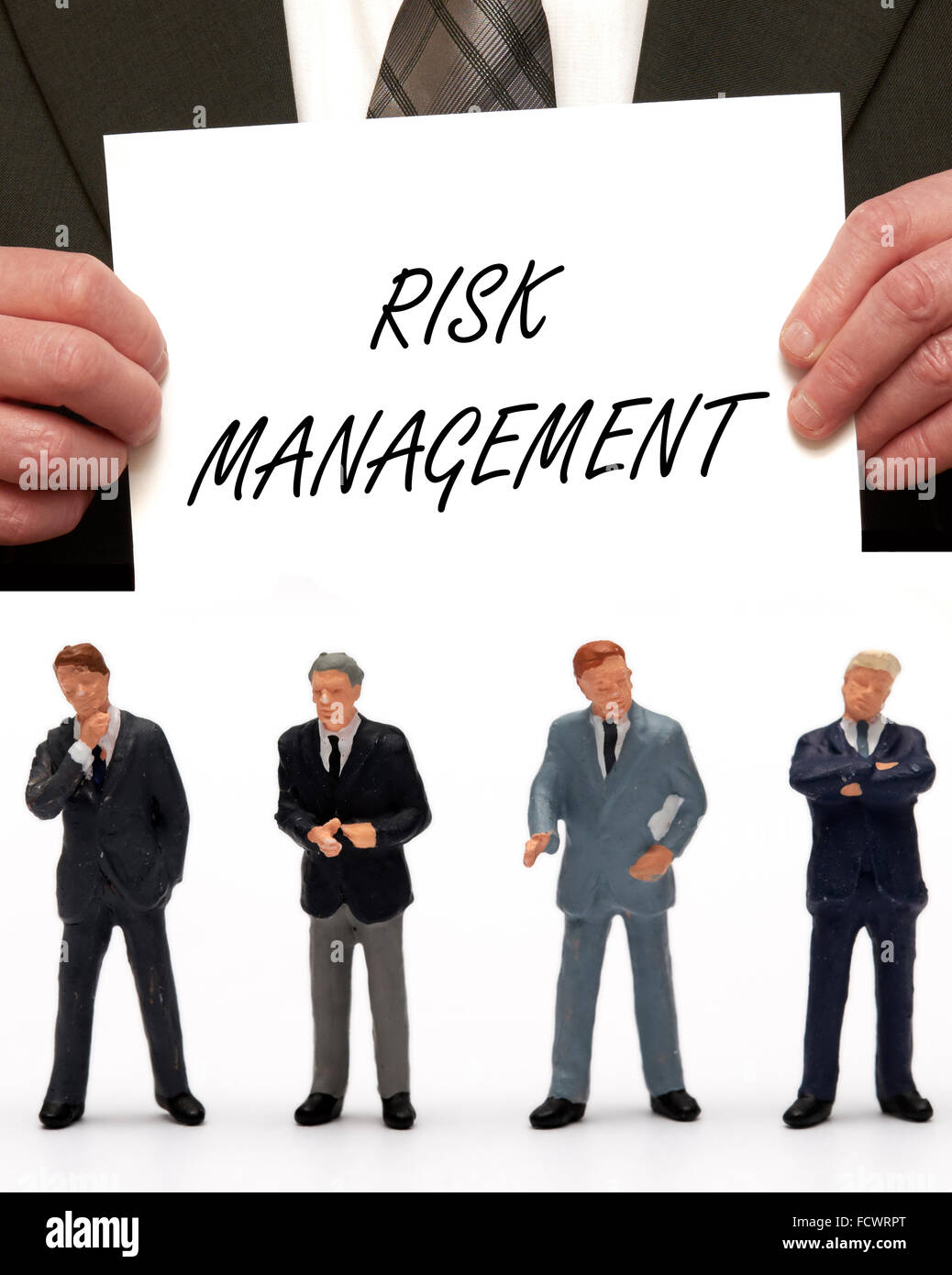 Miniature figurine Business men dressed in suits under the message 'Risk management ' on a card being held - Stock Image