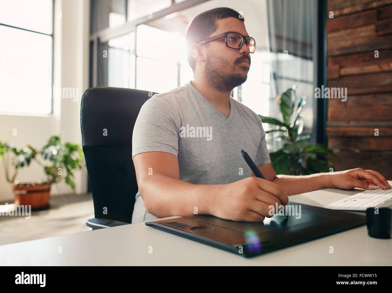 Portrait of young male photo editor at work in his office. Male graphic designer working at his desk using digital - Stock Image