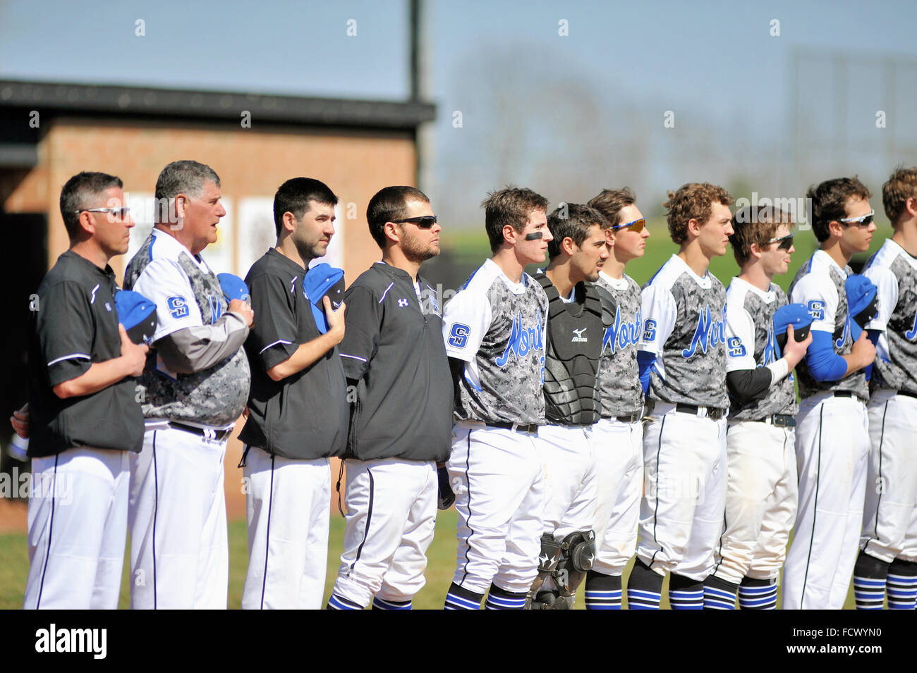 Players and coaches of a high school baseball team line during the national anthem prior to the start of a game. - Stock Image