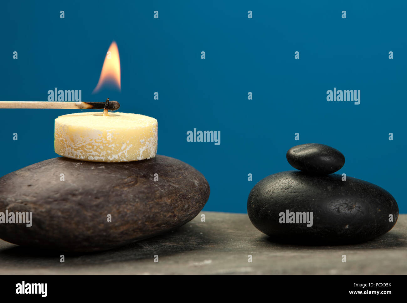 Lighting a tea candle. - Stock Image