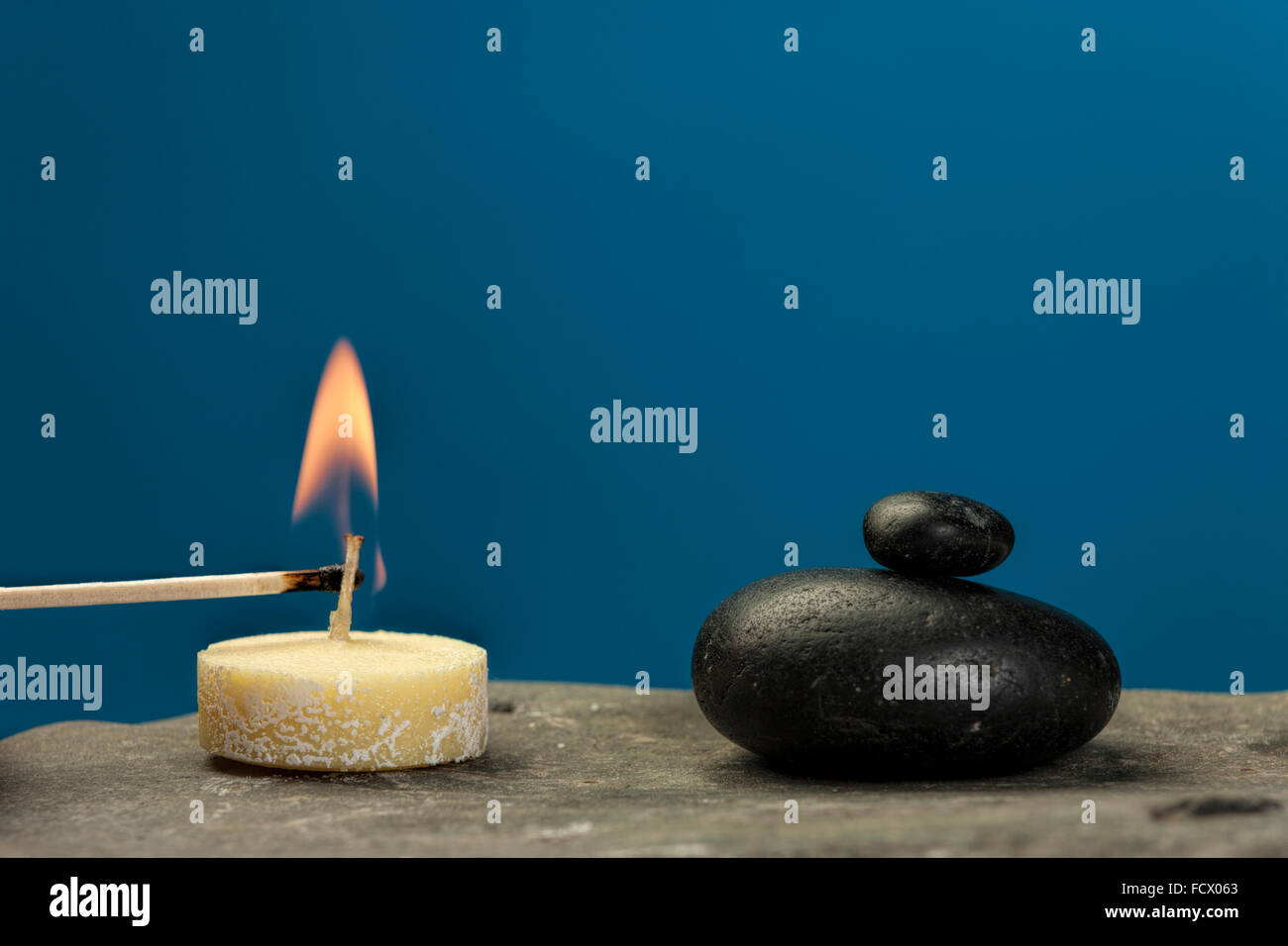 Lighting a small candle on rock. - Stock Image