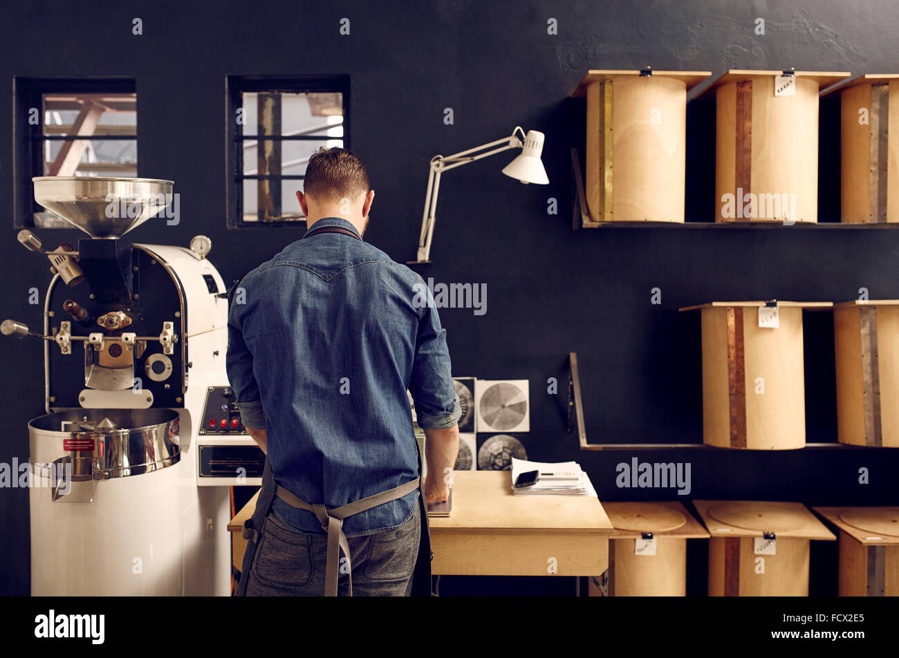 Man working in his modern coffee roastery with neat storage - Stock Image