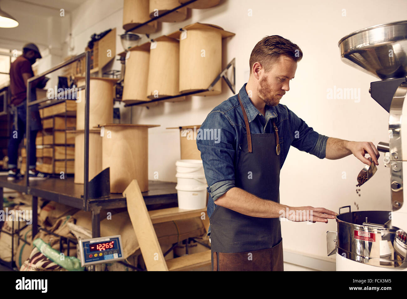 Professional coffee roaster operating a roasting machine in dist - Stock Image