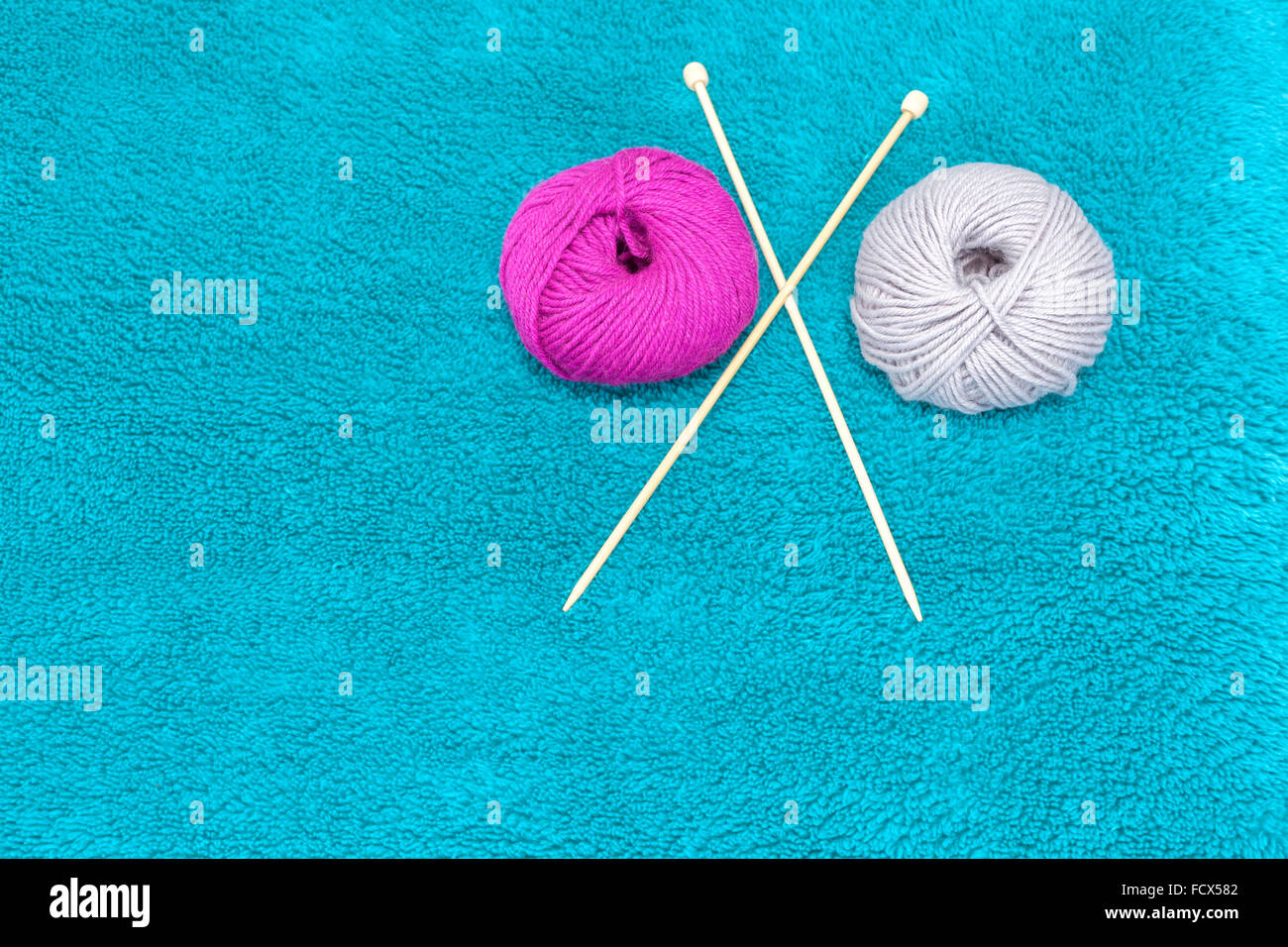 Wool yarns and knitting needles, space for text. - Stock Image