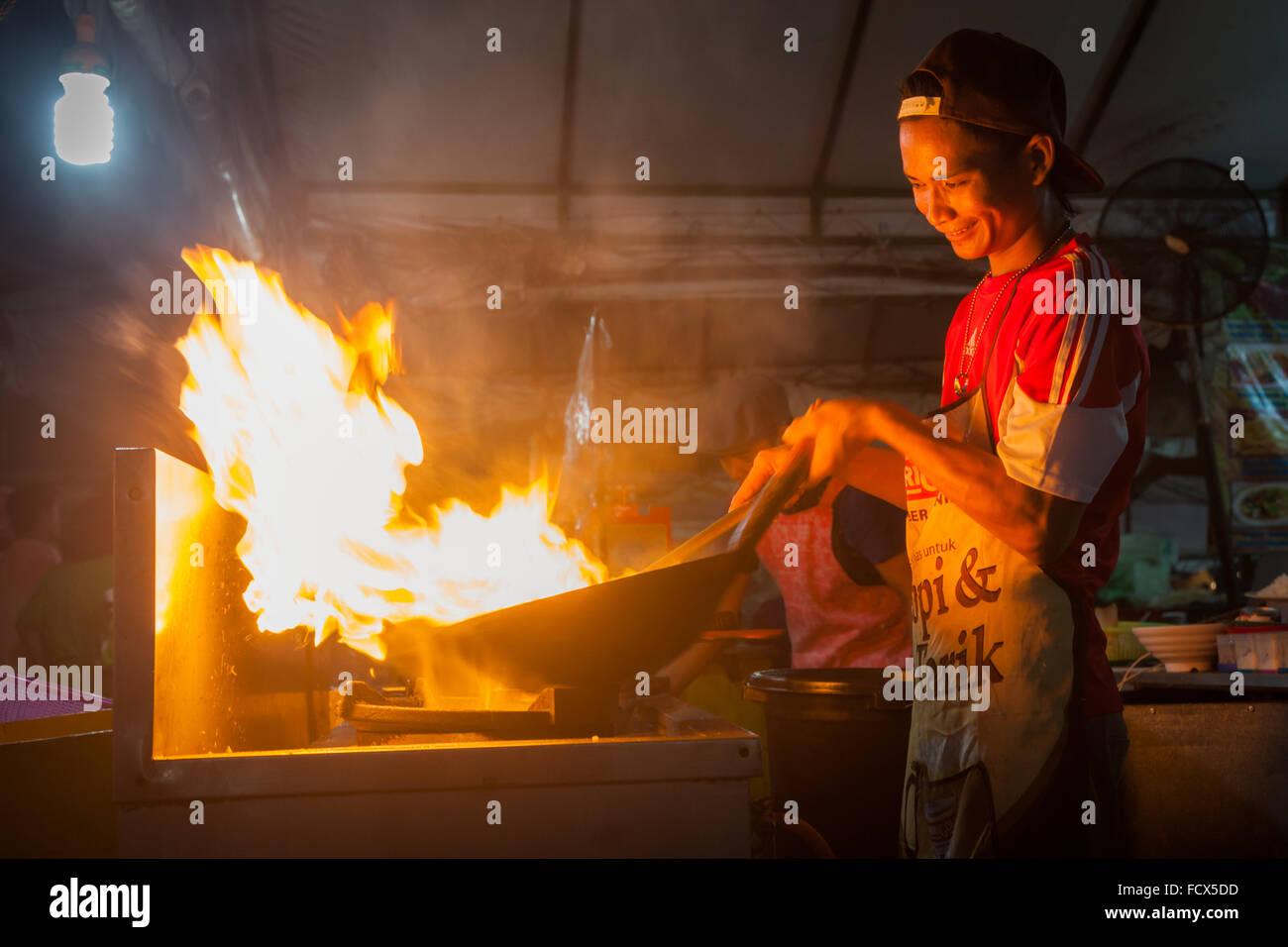 A cook uses a wok frying pan to cook noodles and has flames around his pan, the market, Kota Kinabalu, Malaysia - Stock Image