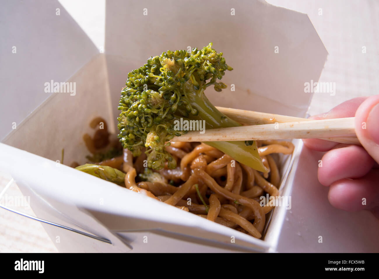 Chinese take out, broccoli held with chopsticks - Stock Image