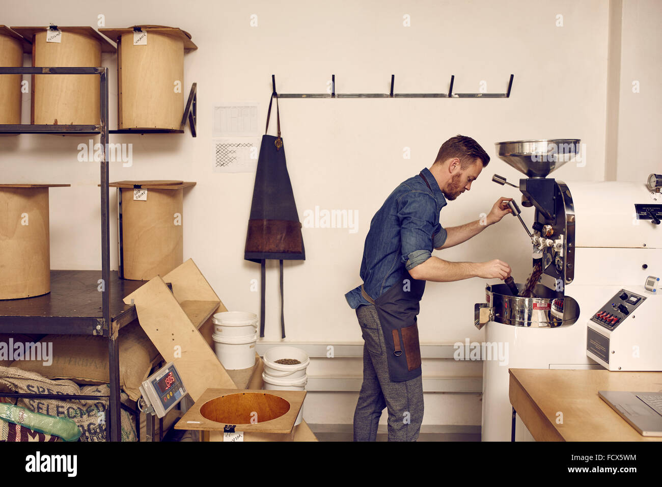 Business owner operating a modern coffee bean roasting machine - Stock Image