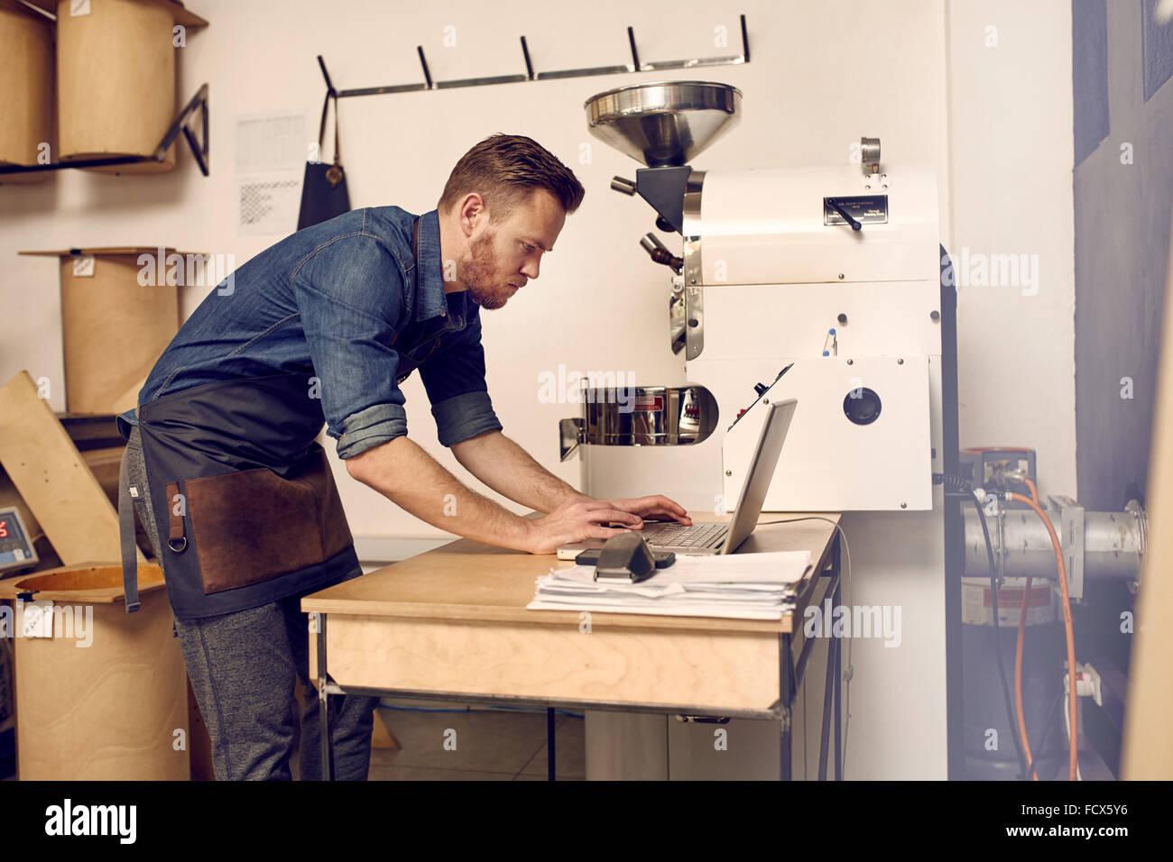 Modern coffee roaster using his laptop alongside a modern roasti - Stock Image
