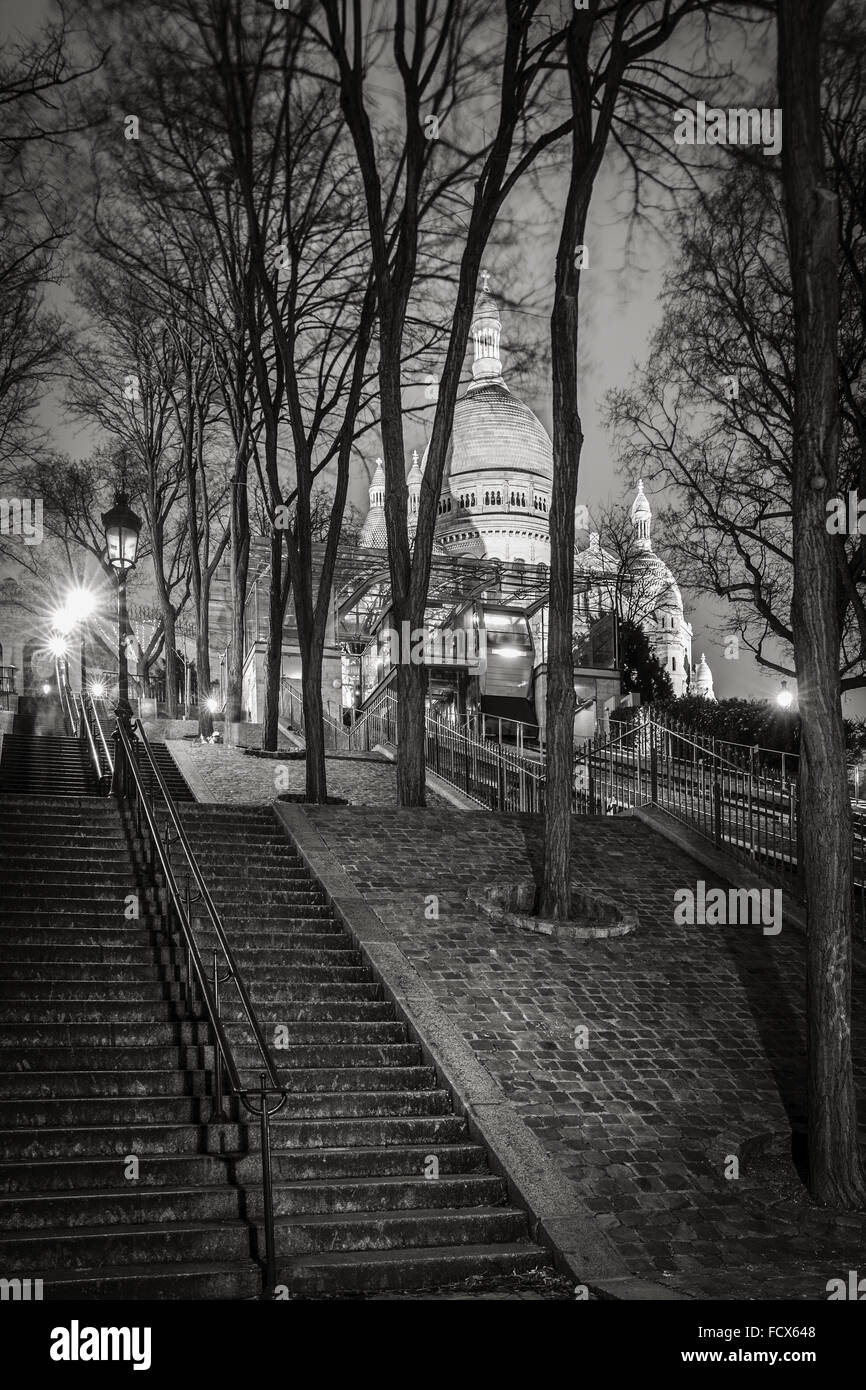 Stairs leading to the Basilica of the Sacred Heart (Sacre Coeur Basilica) at night in Montmartre - Black and White, - Stock Image