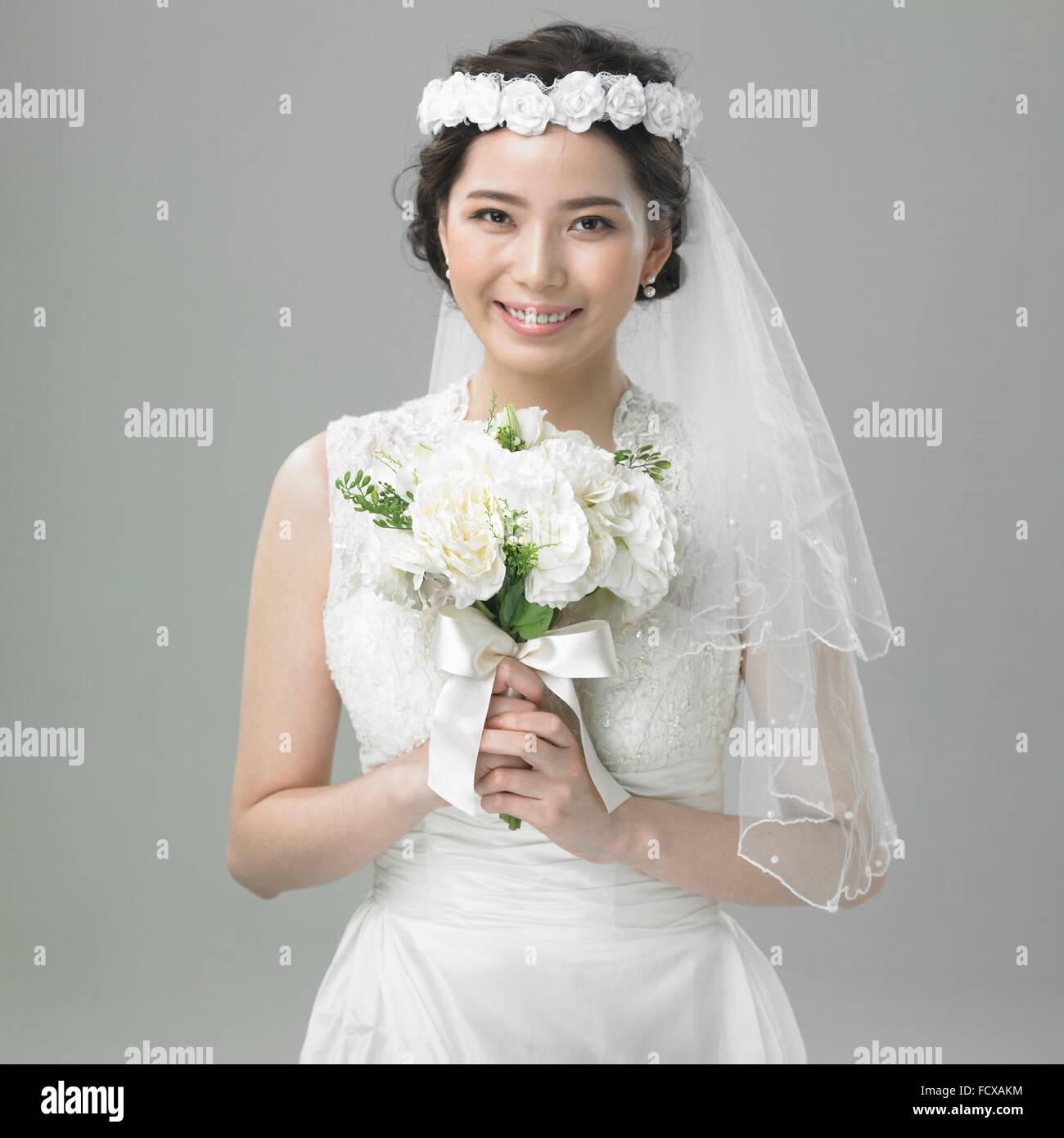 Bride In Flower Crown With Lace Veil Holding A Bouquet Stock Photo