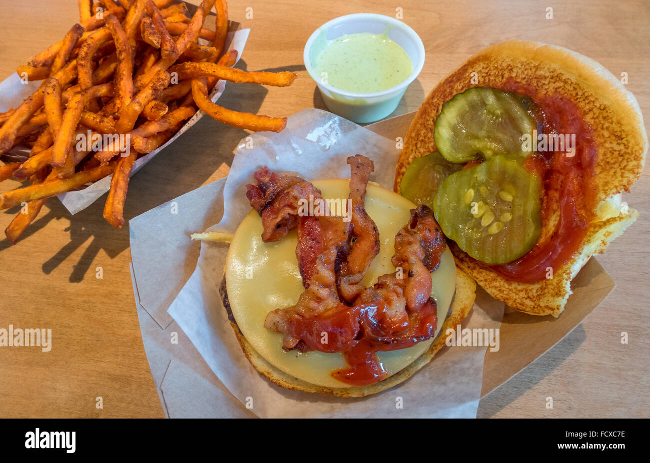 A bacon cheeseburger with ketchup and pickles and sweet potato fries - Stock Image