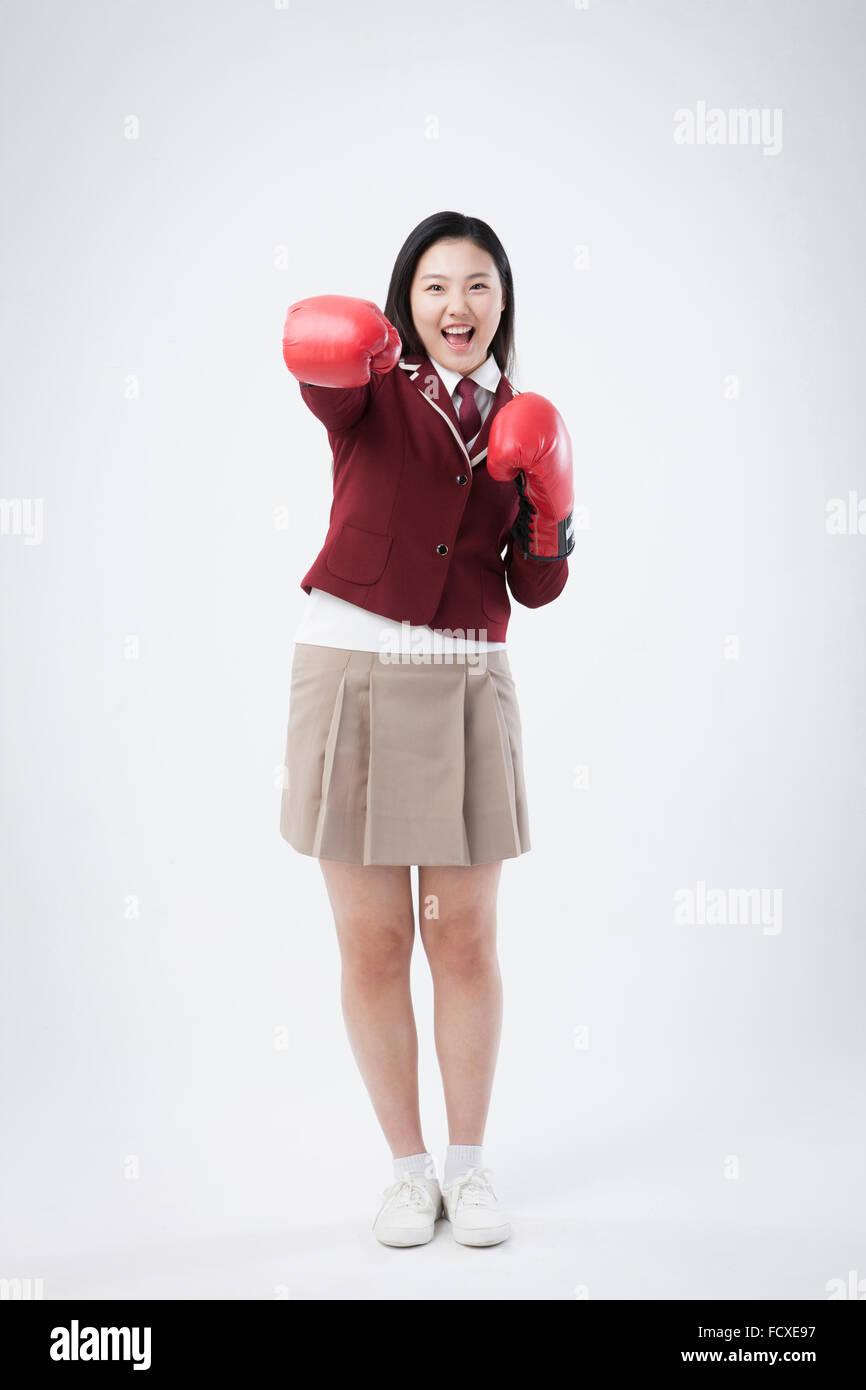 High School Girl In School Uniform Wearing Boxing Gloves