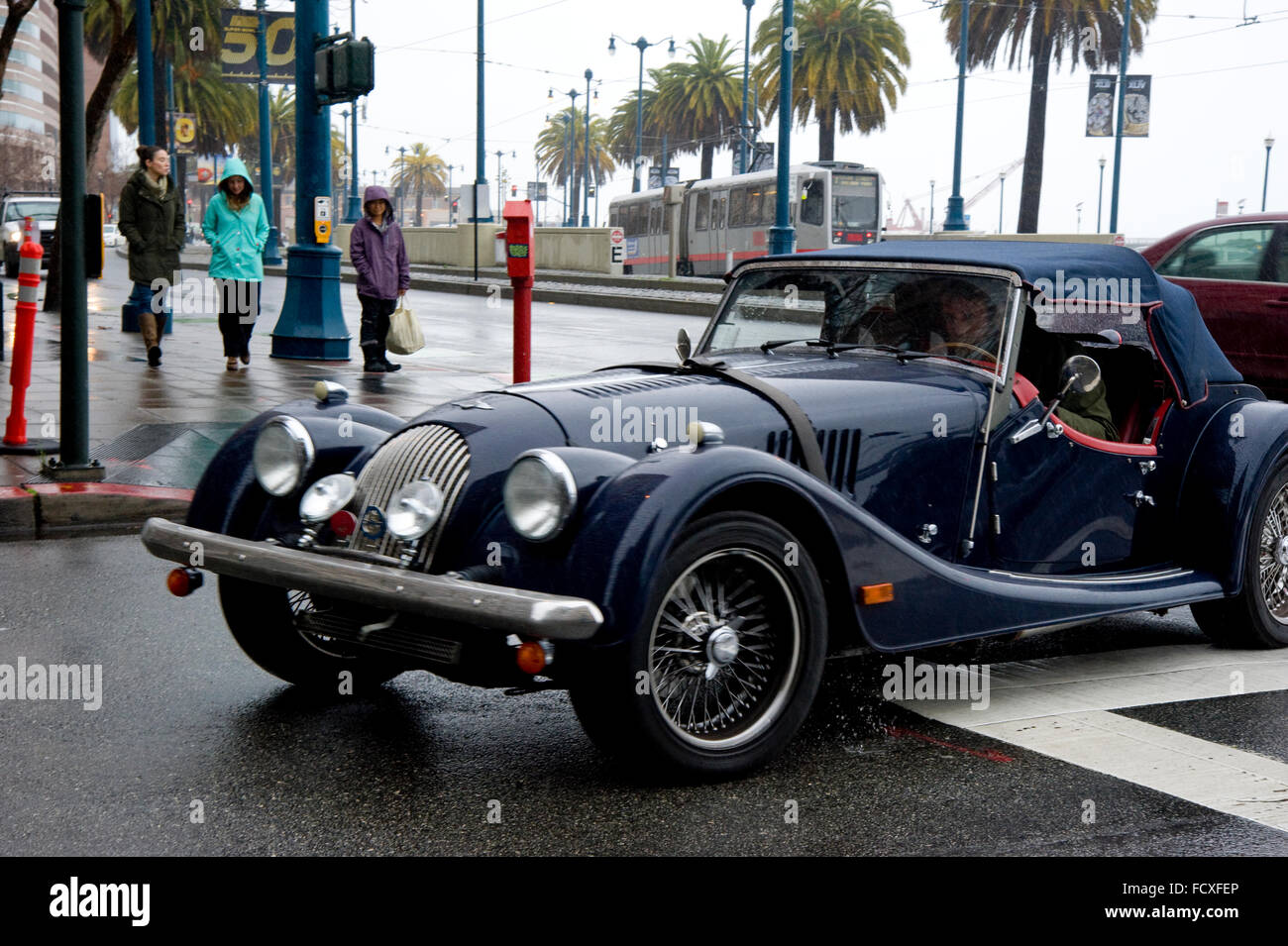 Classic car driving in San Francisco on a rainy day - Stock Image
