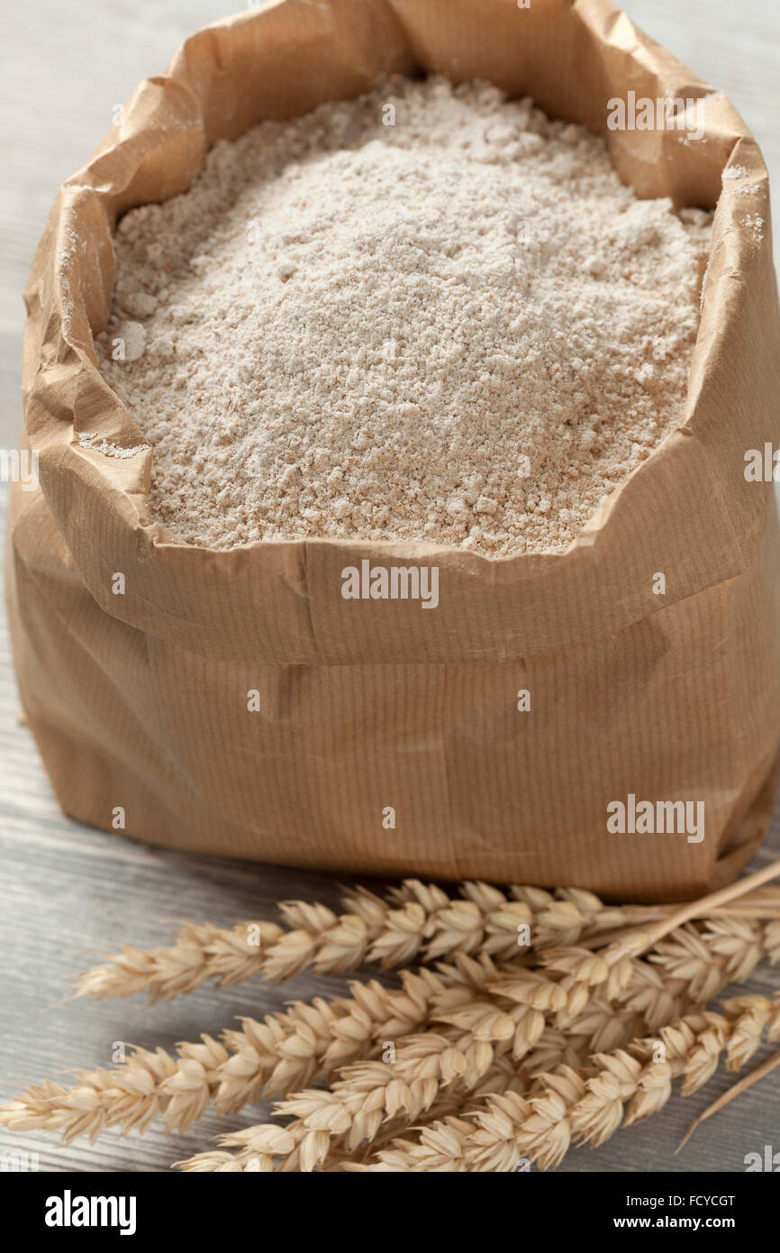 Dried wheat and wheat flour in a paper bag - Stock Image