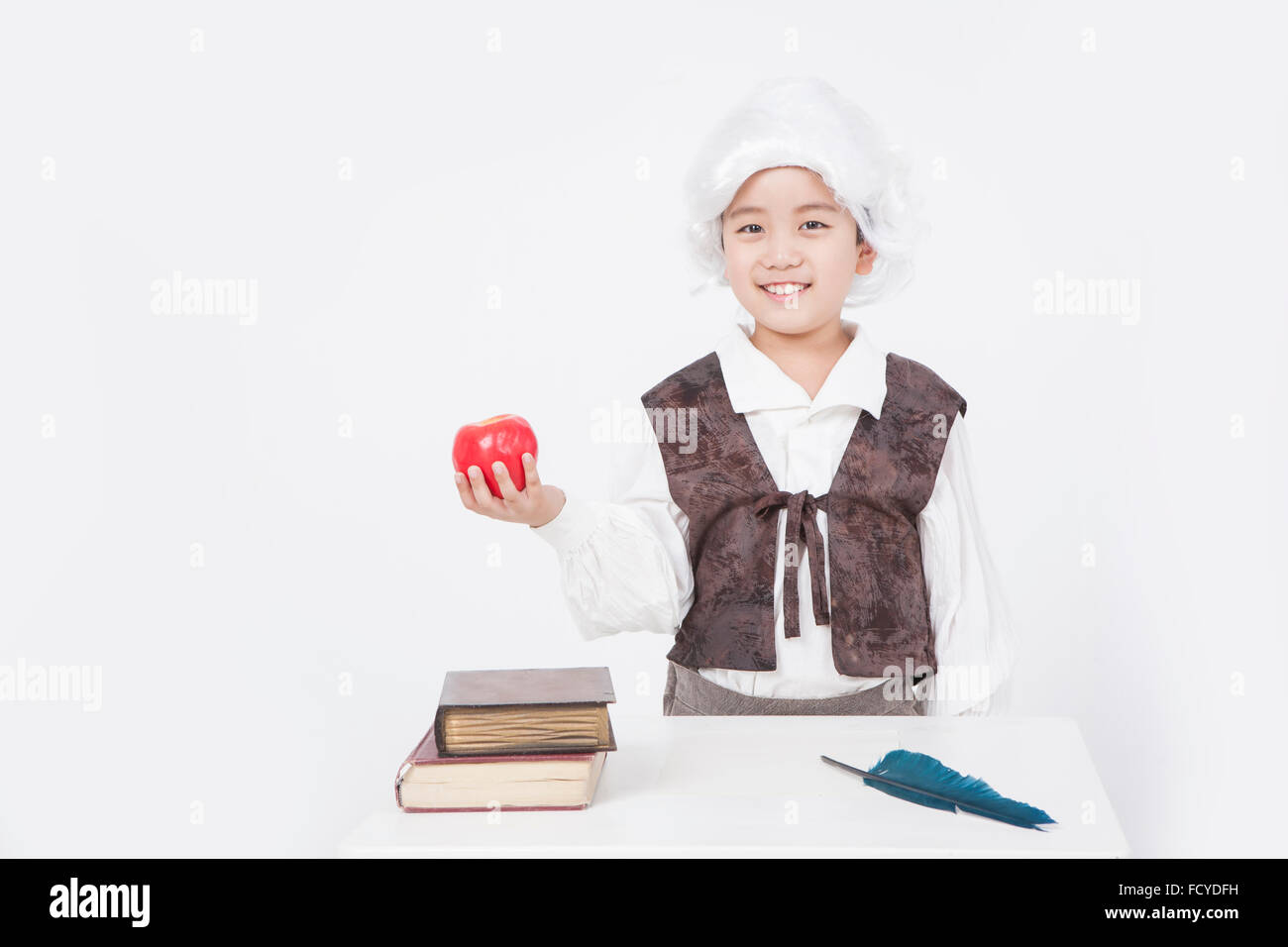 Boy in a classical scholar style holding an apple at desk with old books and a feather pen - Stock Image