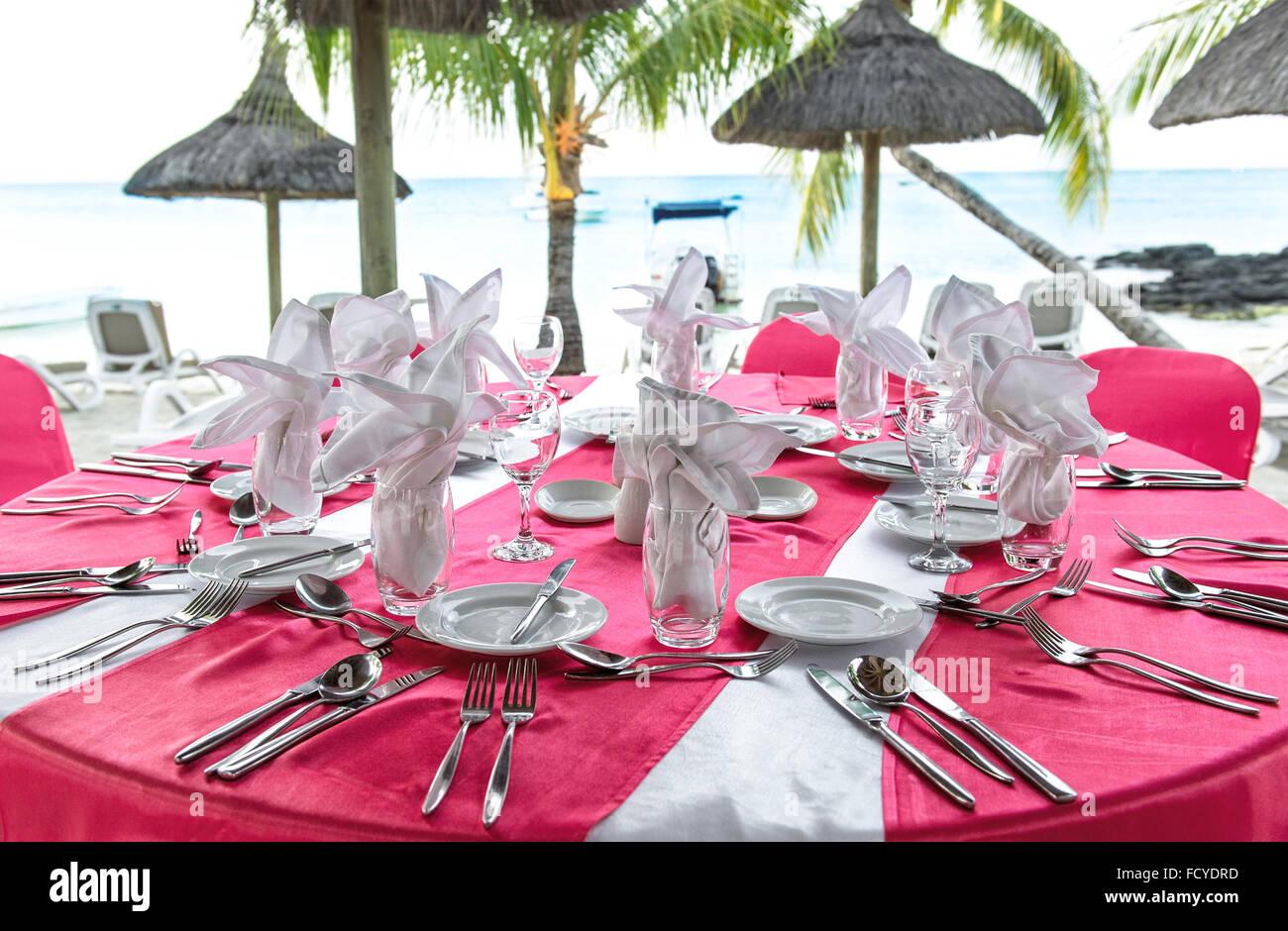 Romantic dinner on sunset beach. Festive pink table place setting ...