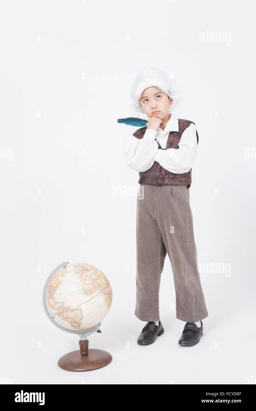 Boy in classical scholar style holding a feather pen and standing behind a globe with the gesture of thinking - Stock Image