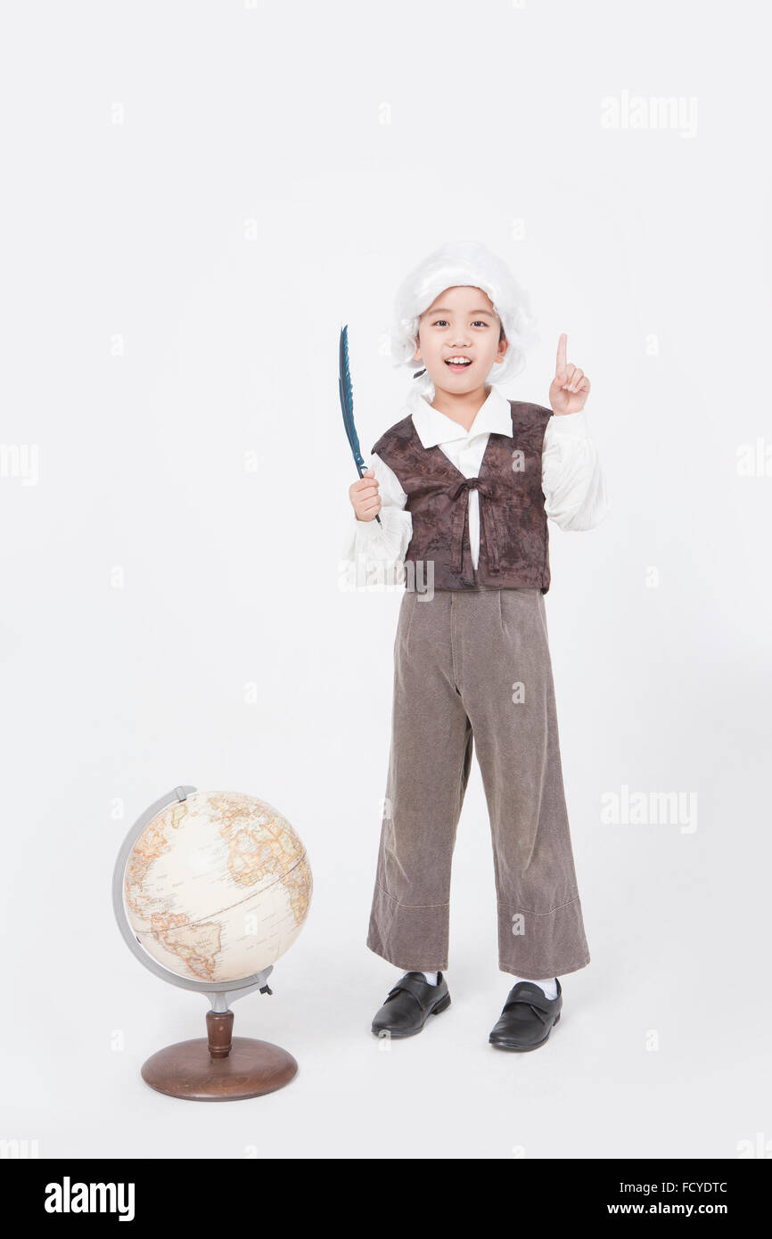Boy in classical scholar style standing behind a globe with a feather pen and with his finger pointing up - Stock Image