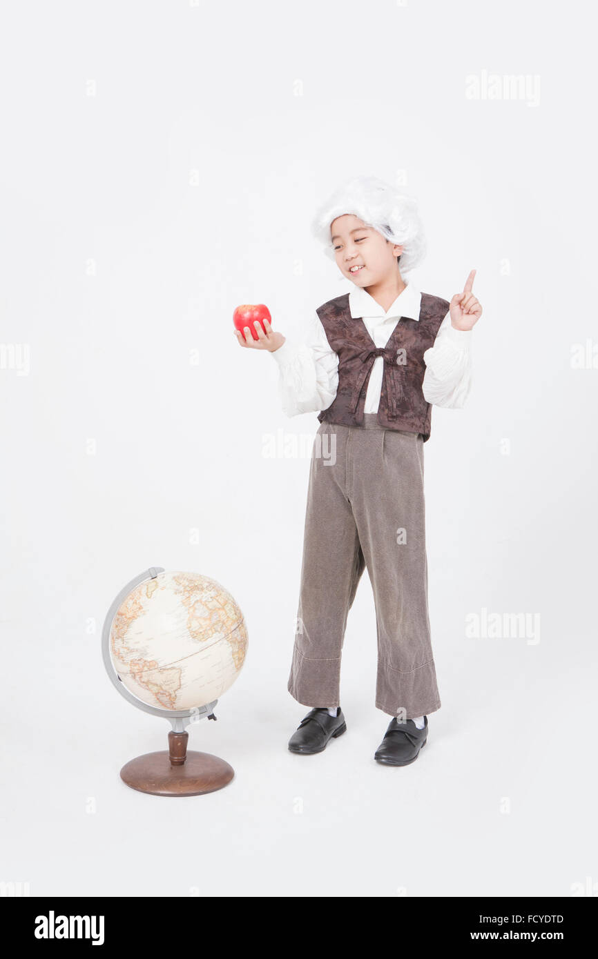Boy in classical scholar style holding an apple with his finger up and standing behind a globe looking down - Stock Image