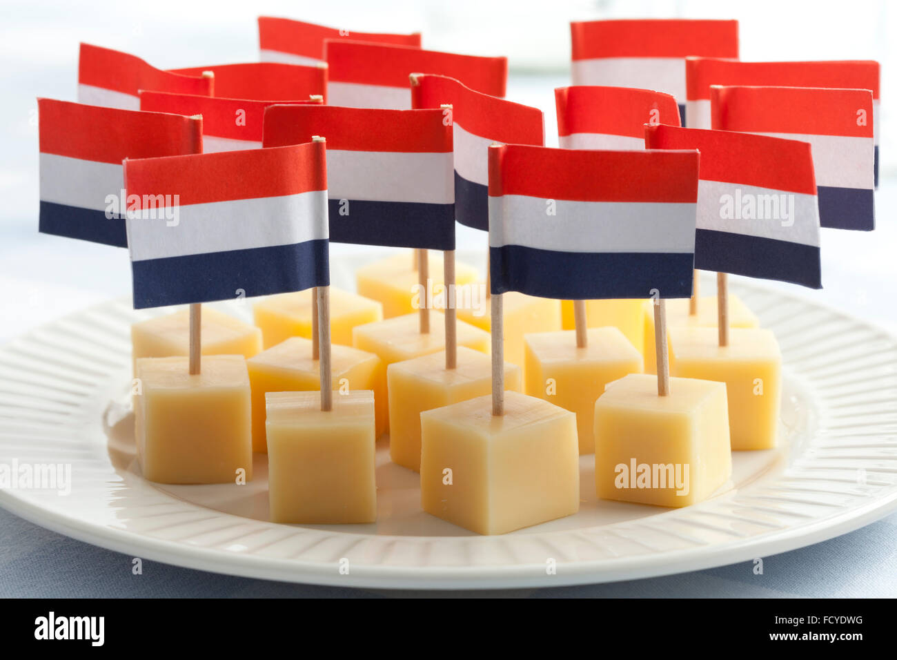 Dish with Edam cheese blocks with flags close up - Stock Image