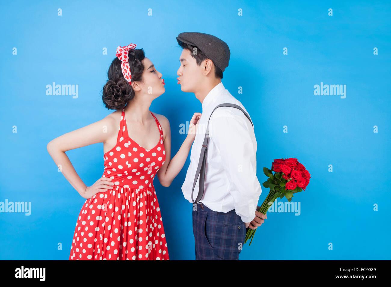 Couple in retro style fashion facing each other with the gesture of kissing and man holding roses behind his back