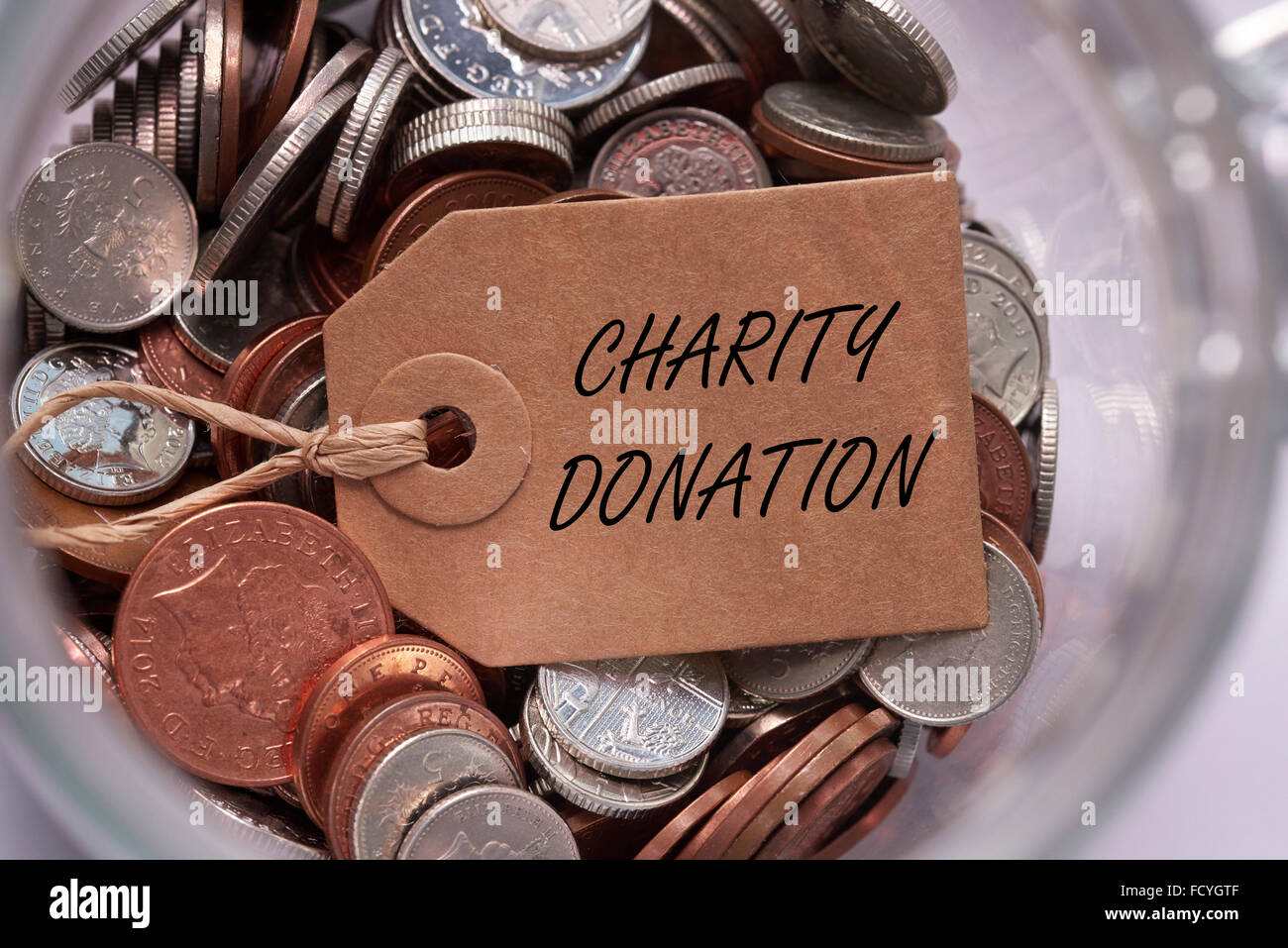 charity donation label on british mixed coins inside a glass jar