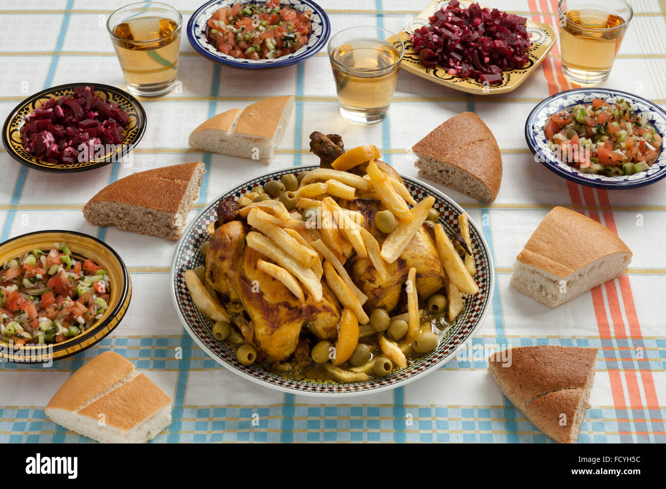 Traditional moroccan stuffed chicken meal with french fries, olives,,preserved lemon,bread and salads on the table - Stock Image