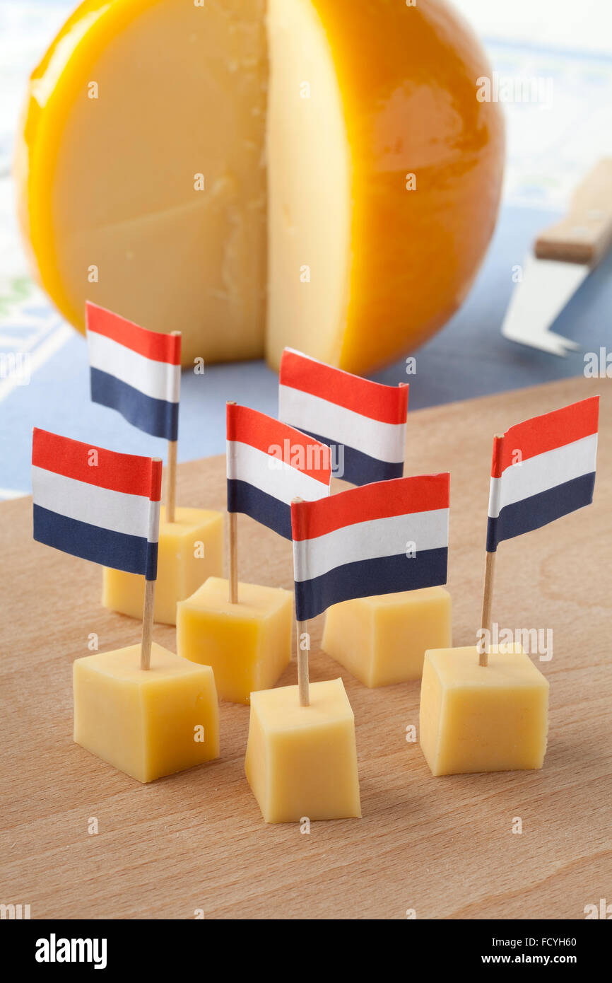 Yellow Edam cheese blocks with Dutch flags as a snack - Stock Image