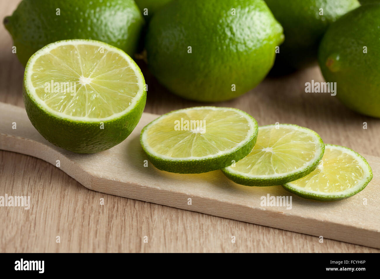 Fresh cut green limes on a cutting board - Stock Image