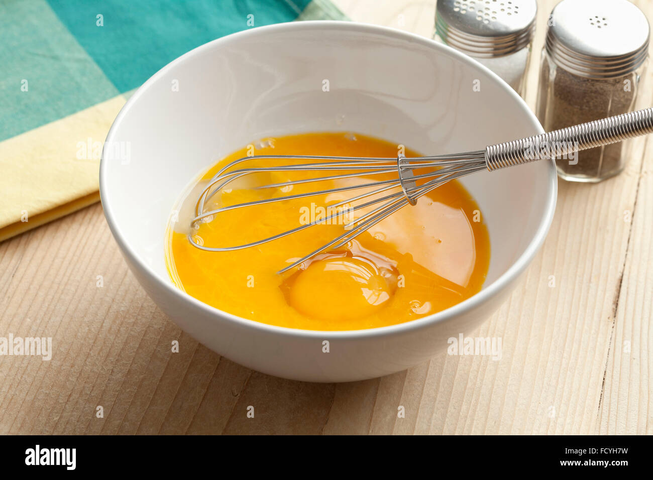 Beaten egg yolks in a bowl with whisk - Stock Image