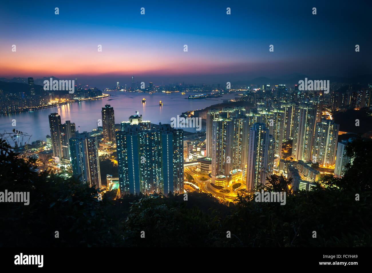 Illuminated high-rise apartment blocks in Yau Tong as seen from Devil's Peak, Kowloon - Stock Image